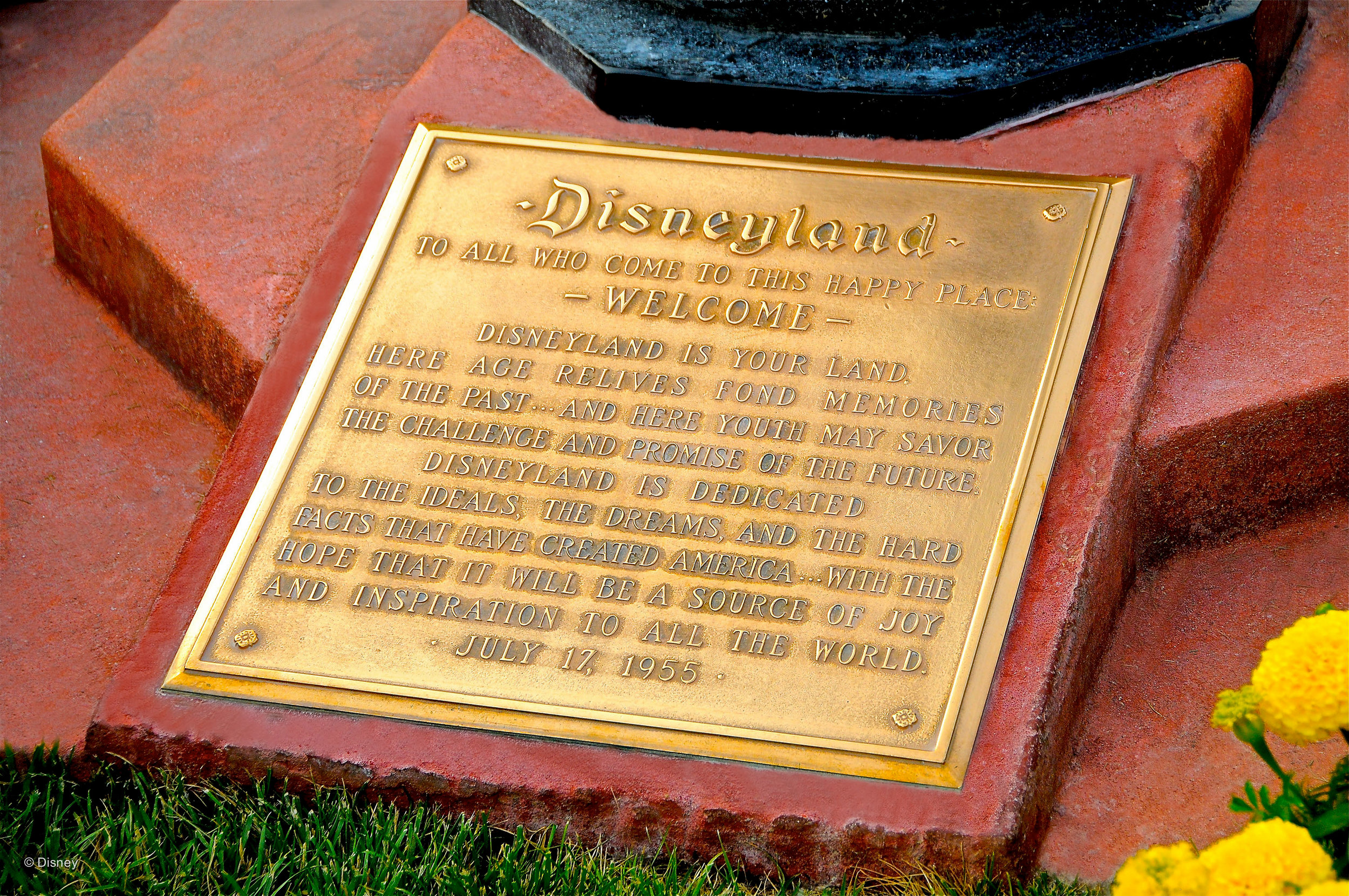 The Disneyland dedication plaque located at the flagpole on Main Street.
