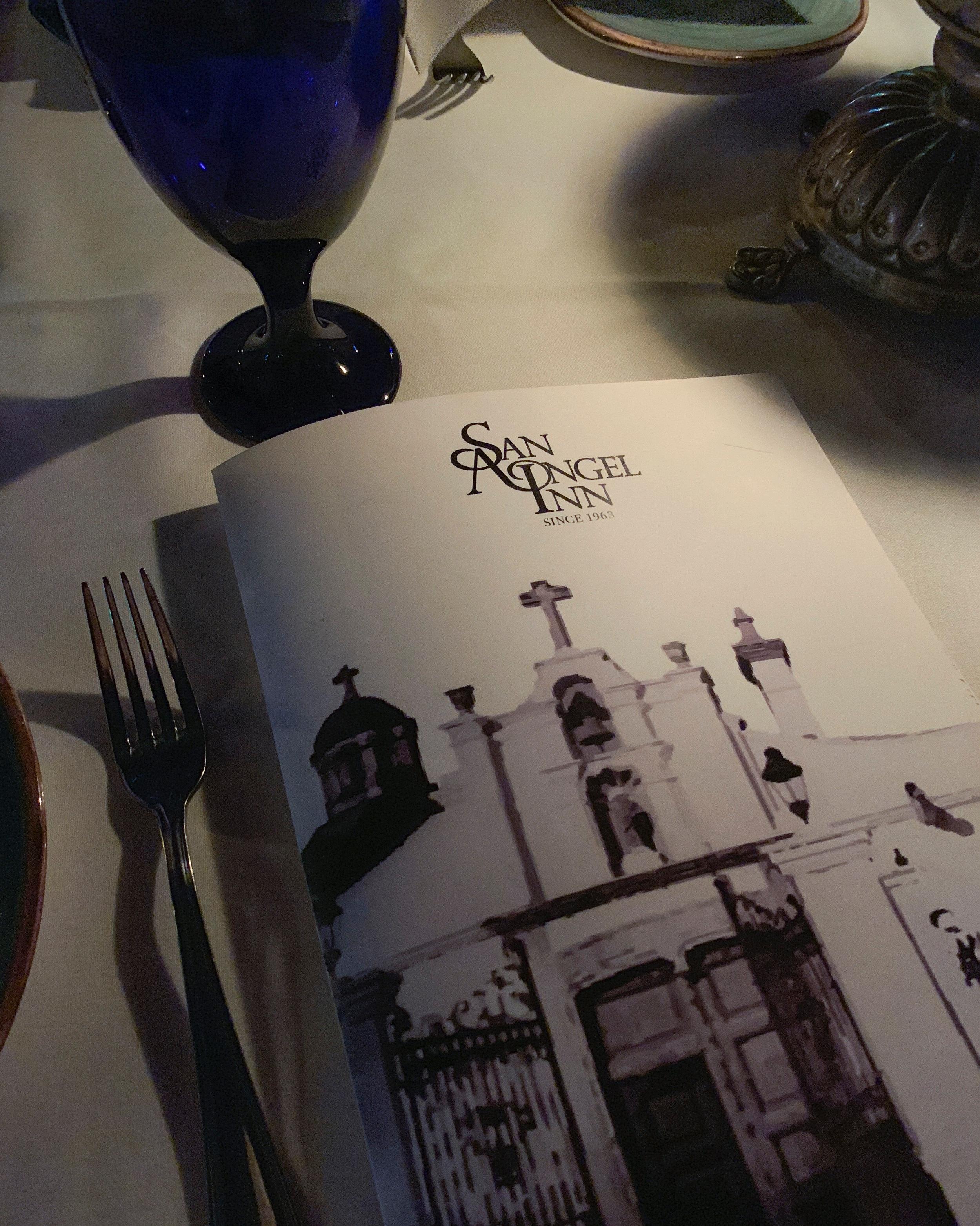 A menu illuminated by candle light.