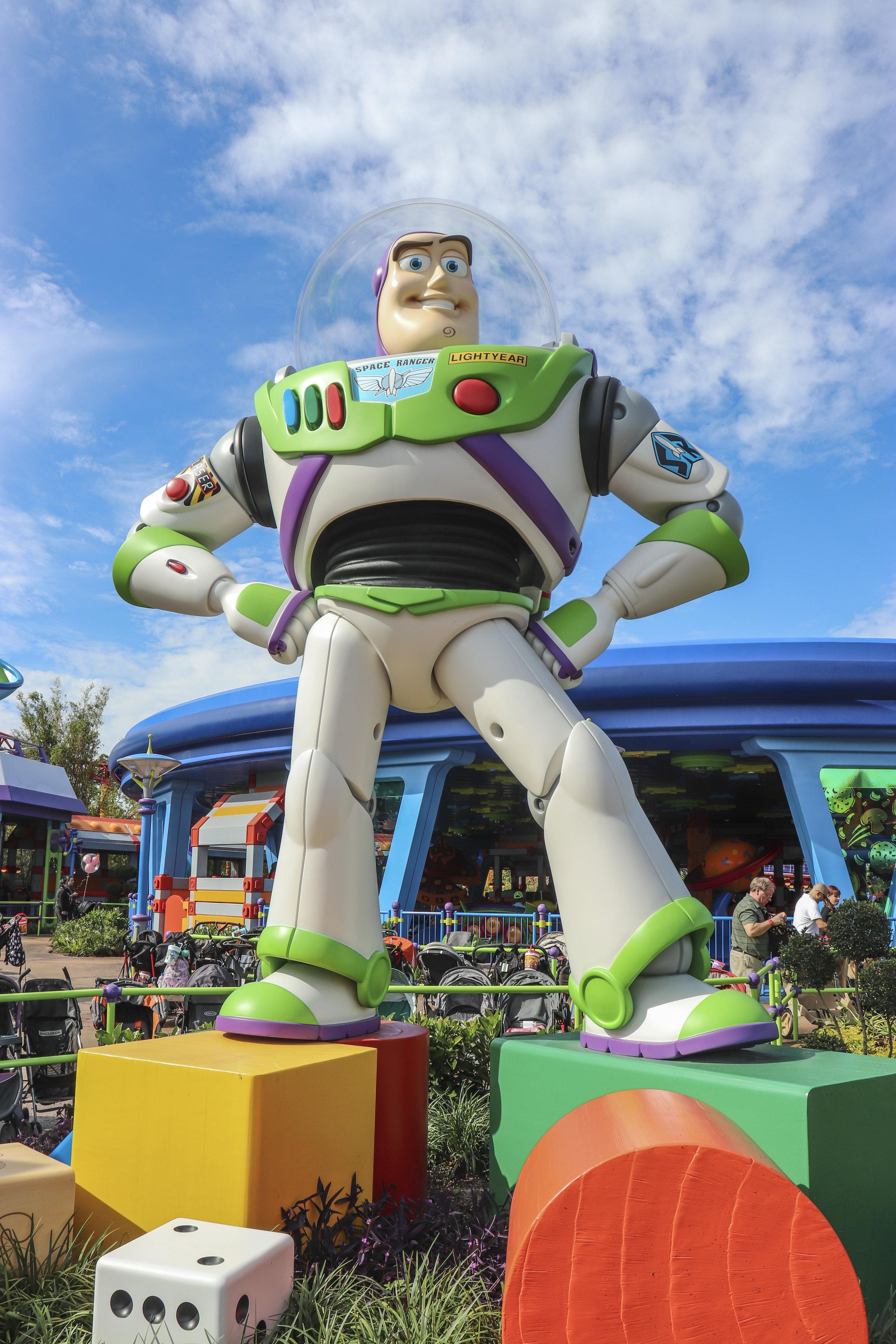 Buzz Lightyear stands outside of Alien Swirling Saucers.