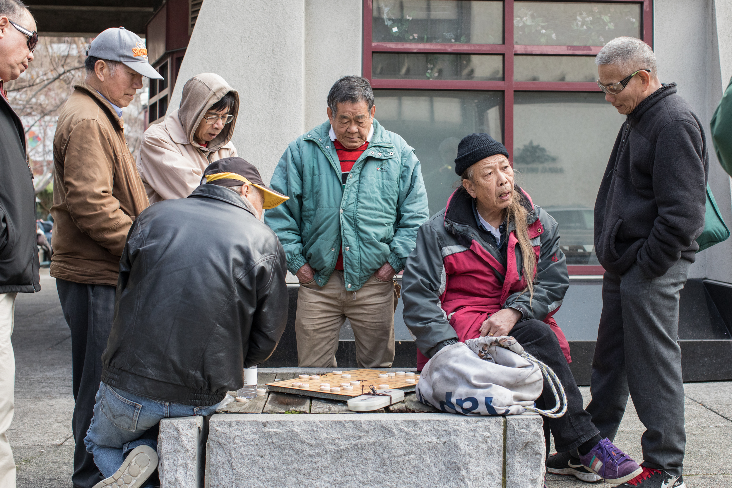 Elderly immigrants play Xianqi (Chinese chess) in Portsmouth Square, San Francisco. The city's Chinatown is still the most densely populated urban area west of Manhattan. Many families live in single rooms: the square is the community's garden.