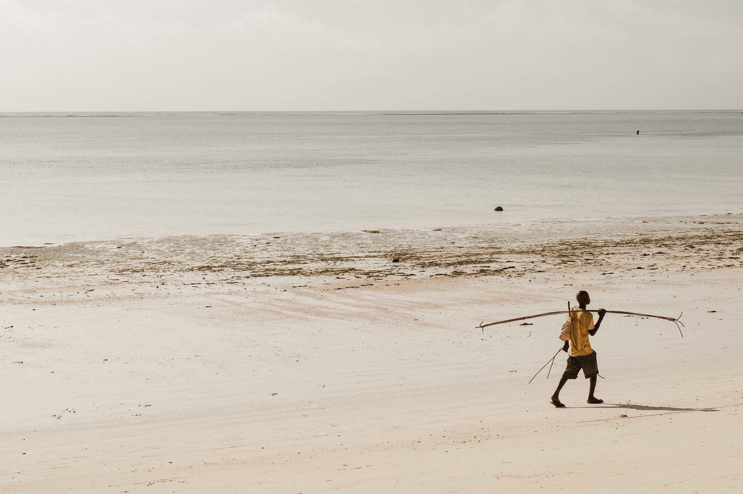 A spear fisherman packs up for the day and heads home along the beach with his catch
