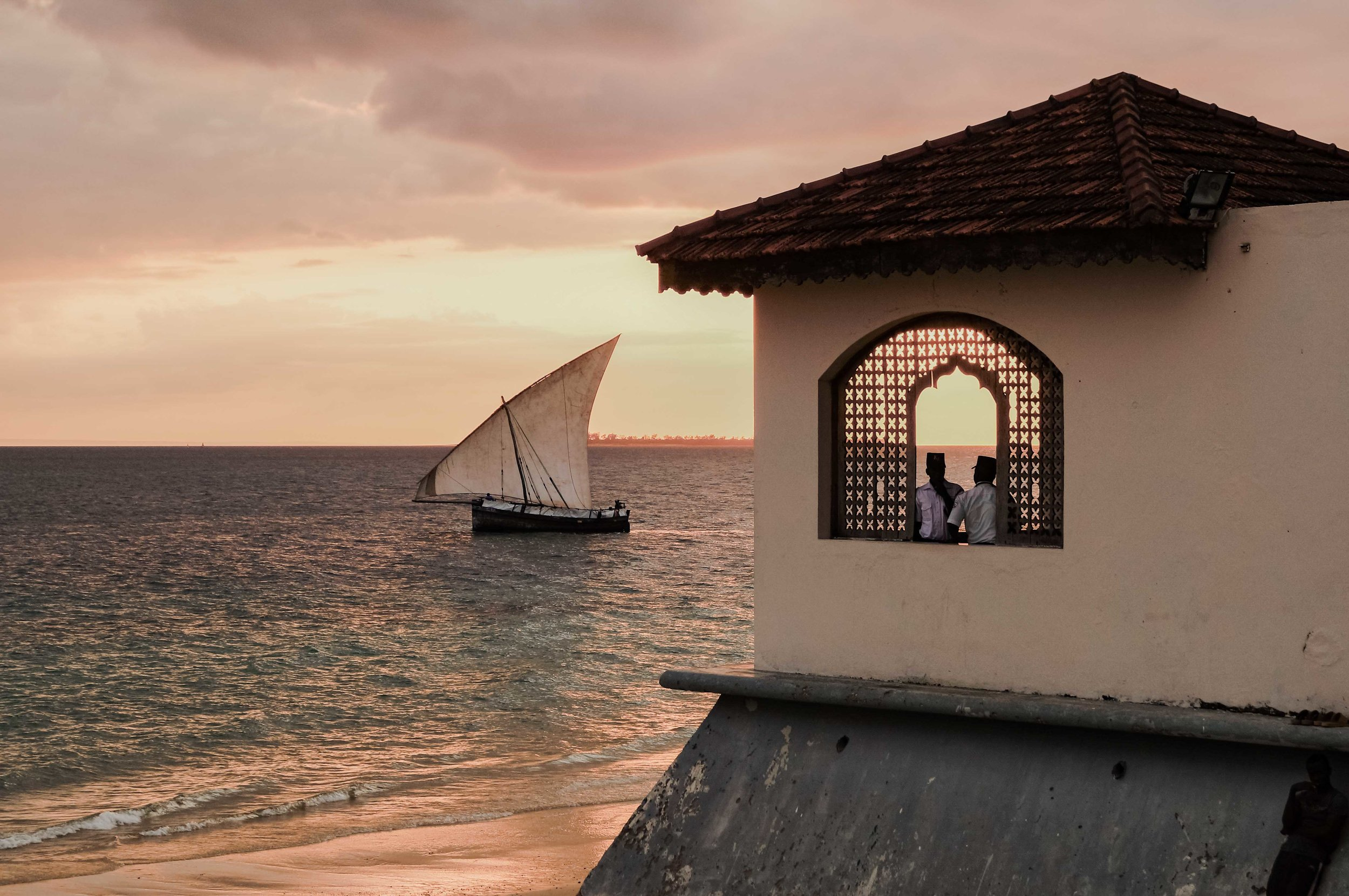 As sun sets the dhow boats glide back to port across the golden waters