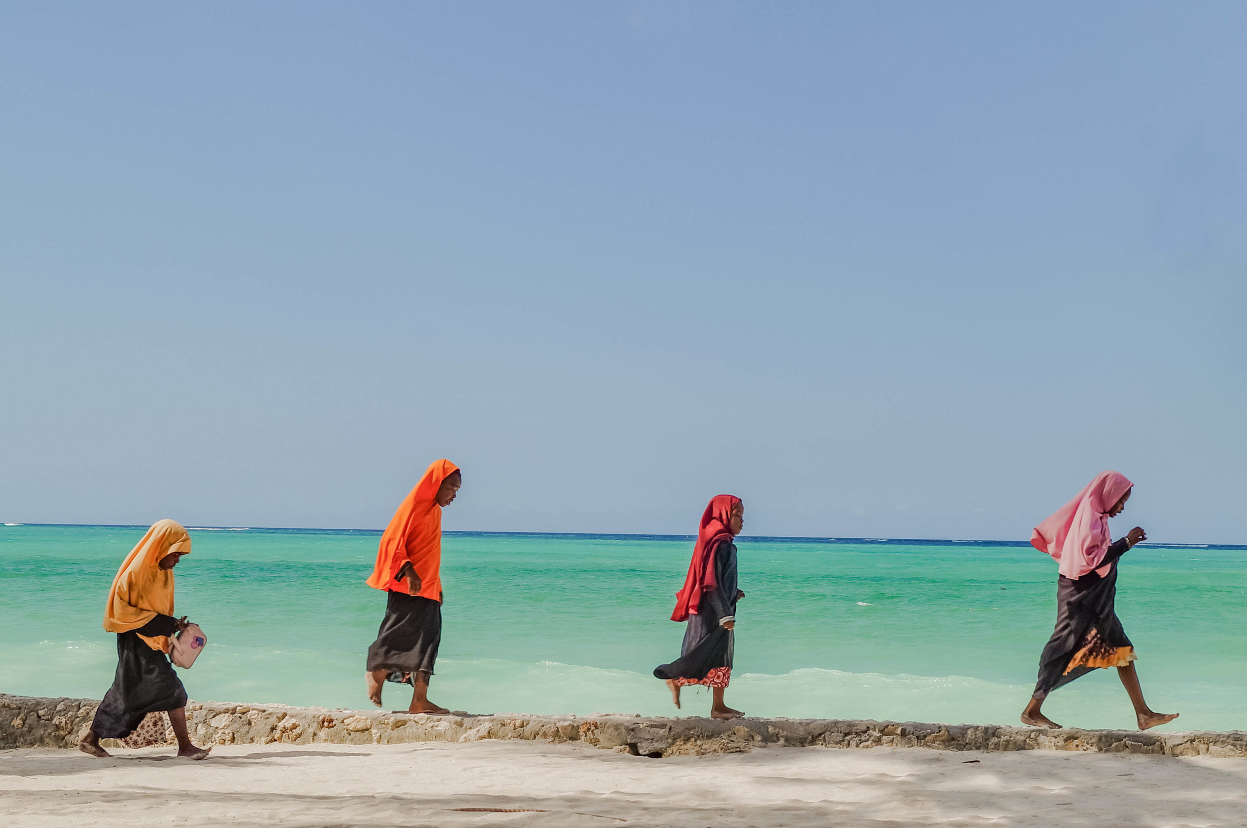 Young girls dressed in colourful hijabs make their way home from school along the beach front rock walls.