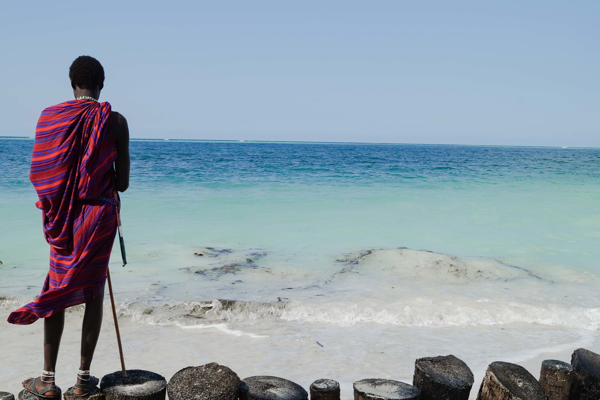 Pristine blue waters set the backdrop for life on Zanziba. Here a Massai man works as a security guard, watching over a hotel that sits on the beachfront.