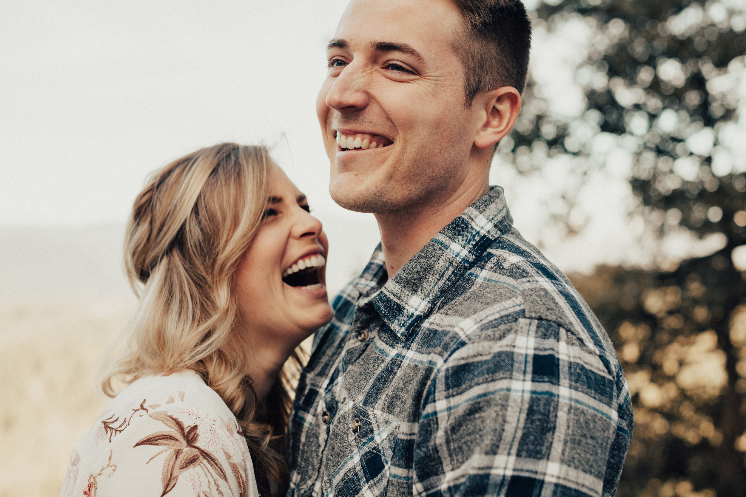 Couple laughing hysterically together during their engagement session.