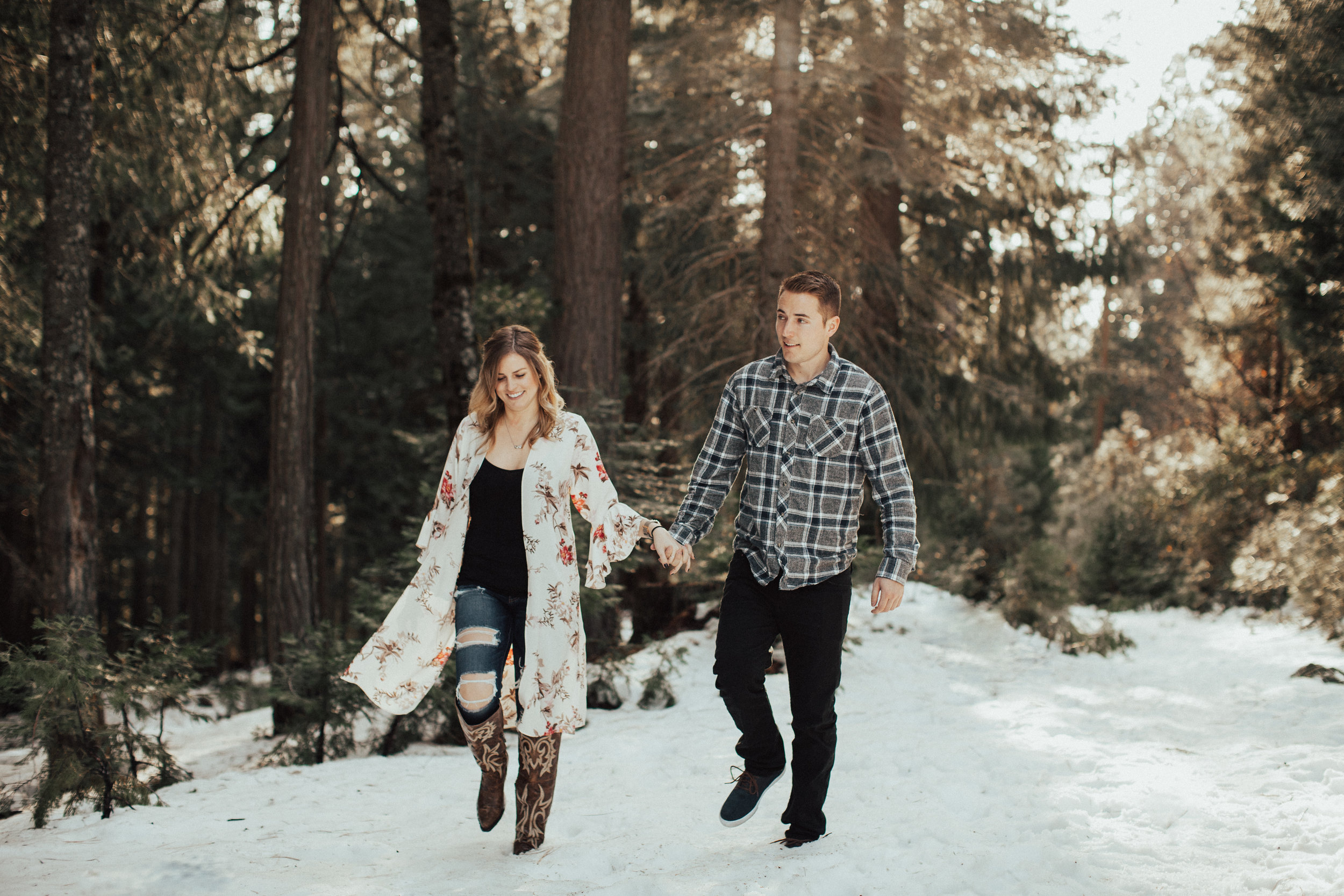 Couple holding hands in front of the large green pine trees in Northern California.