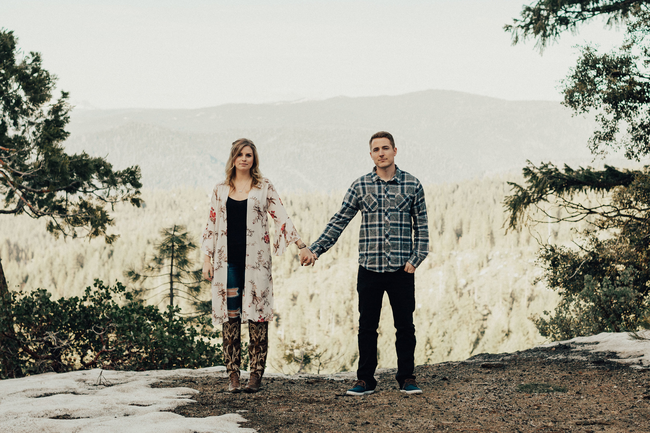 Couple holding hands in front of the Tahoe pine trees.
