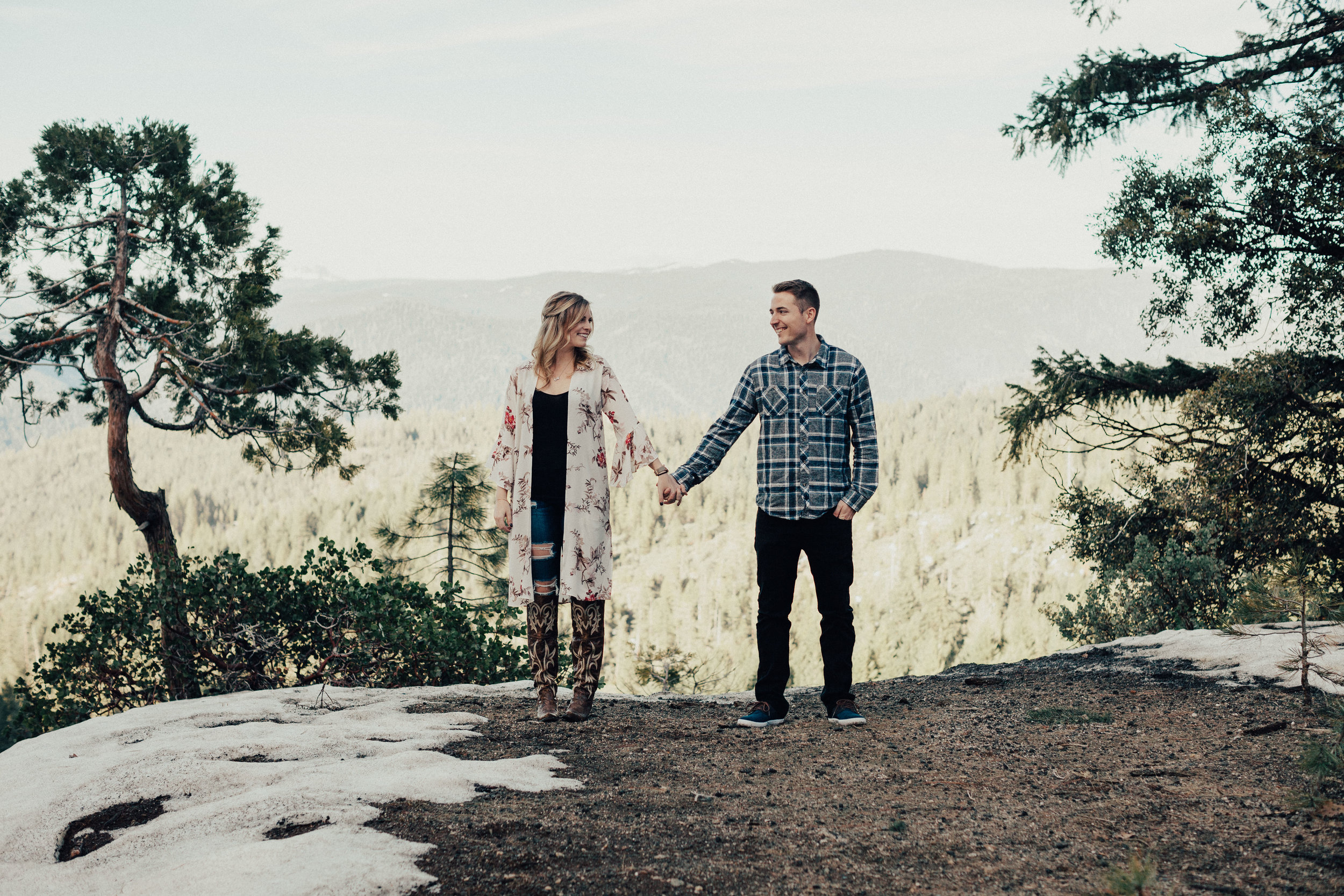 Lovers holding hands in front of the Nevada City Vista Point lookout.