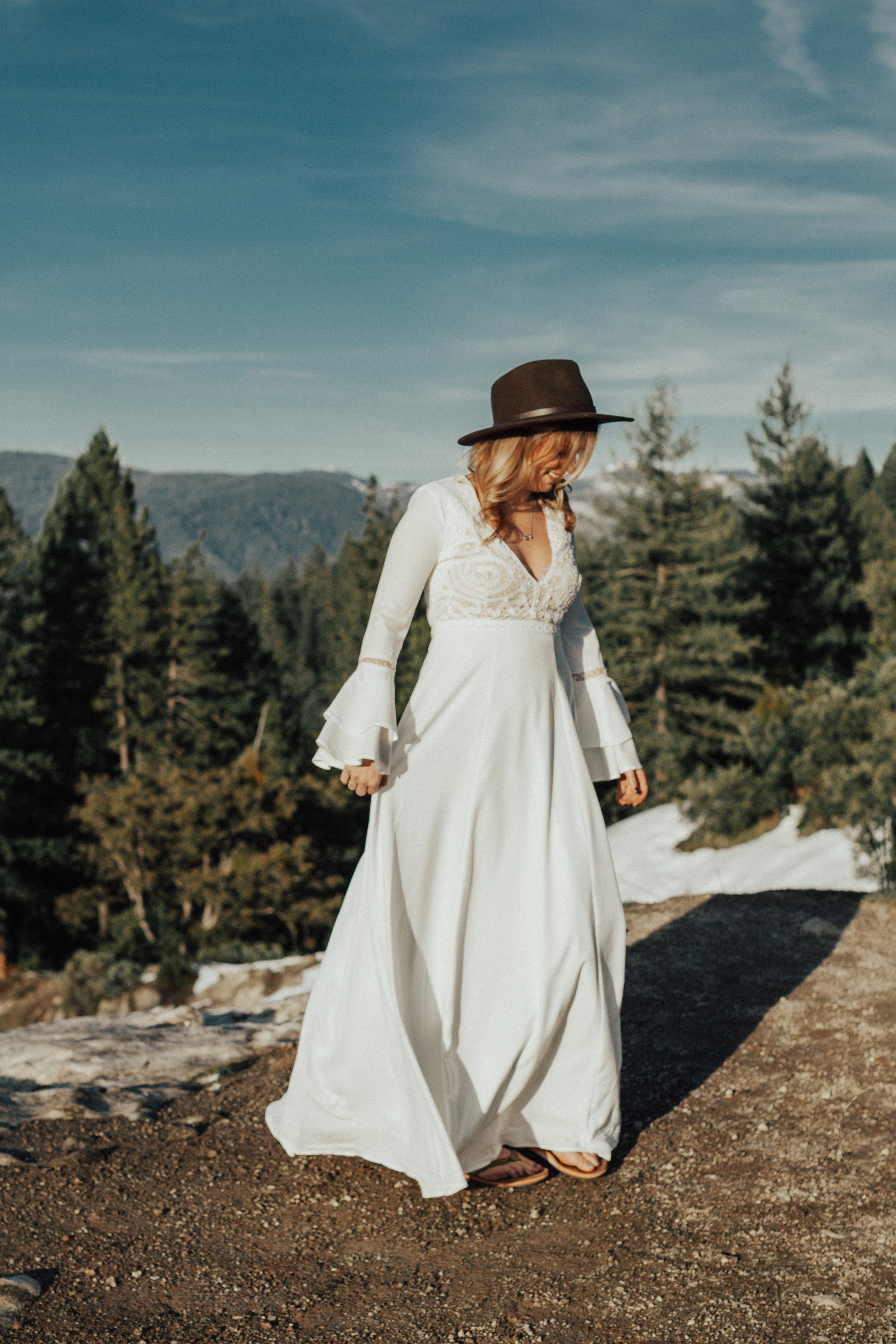 Nevada City bride twirling in her wedding gown in front of the snow capped mountains.
