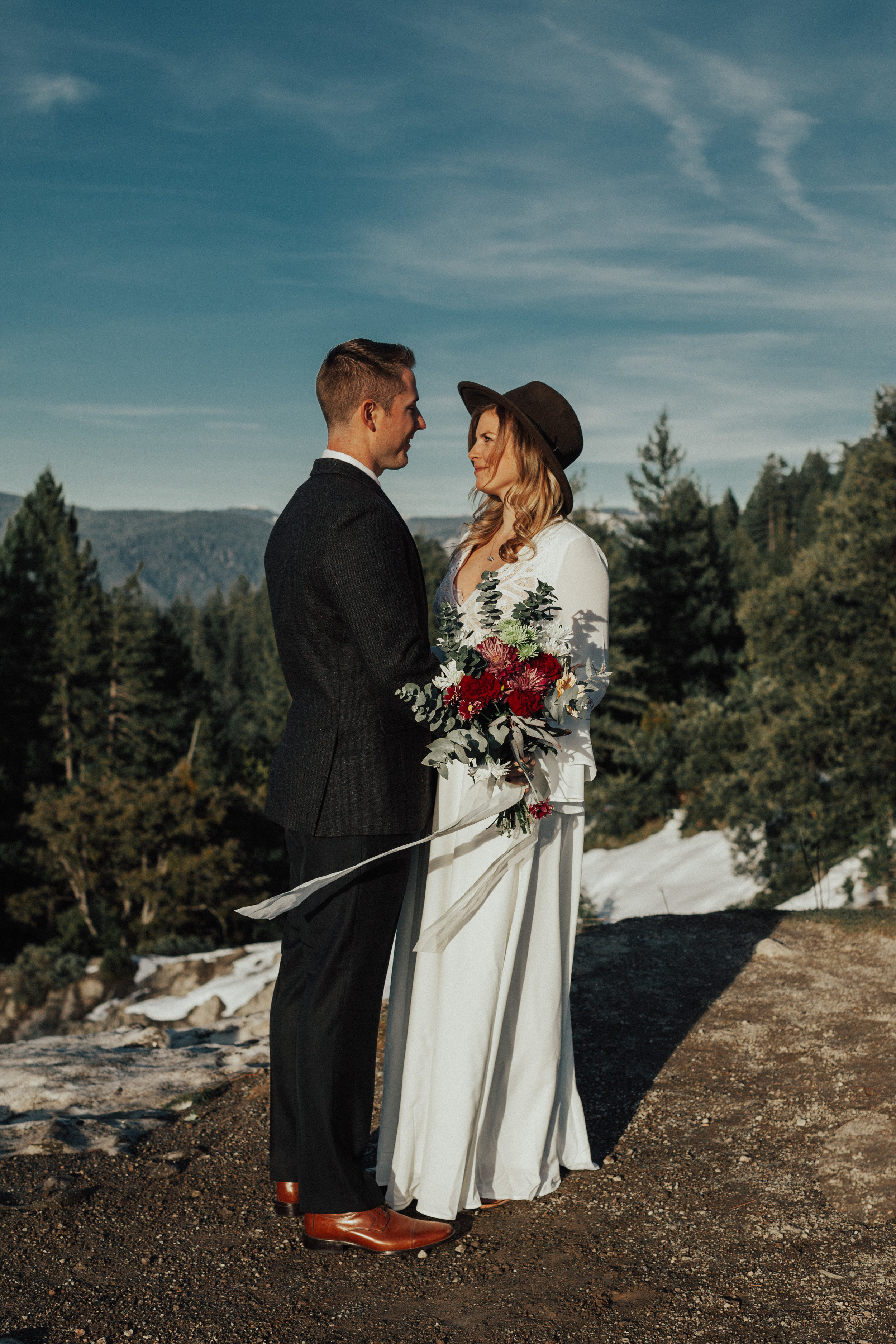 Bride and groom leaning in towards each other and smiling as they overlook the mountain tops.