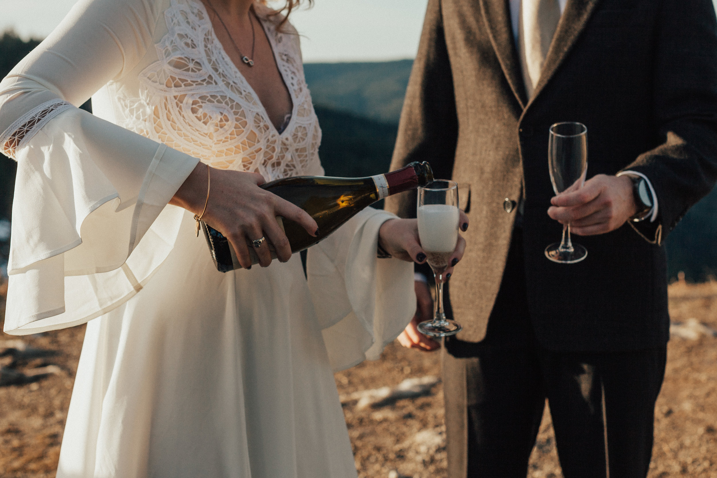 Cropped photo of bride pouring champagne into their glasses. Her wedding dress has the most beautiful bell sleeves that catch the sunlight.