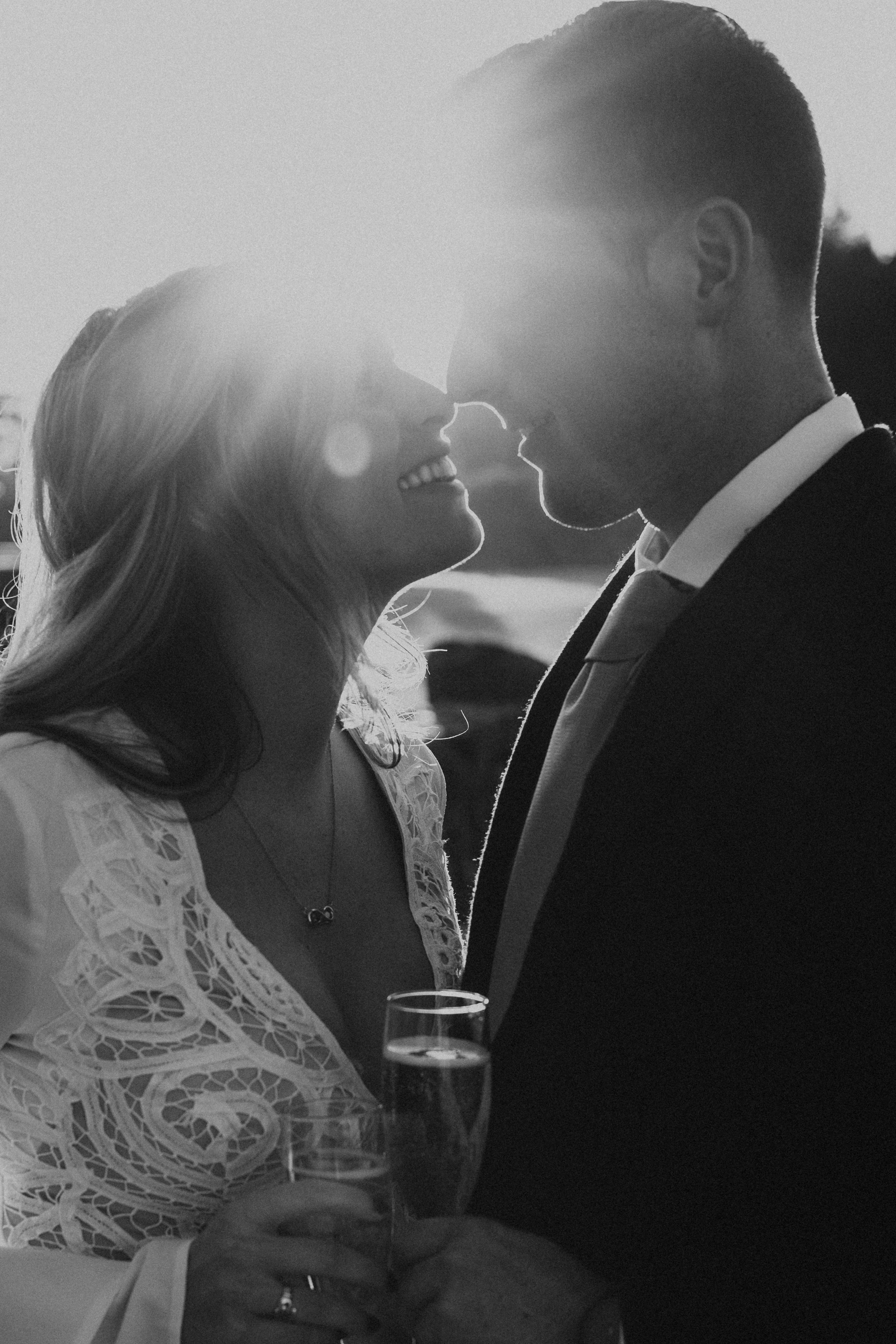 Black and white photograph of newlywed couple touching noses. The sunlight leaking through in the background.