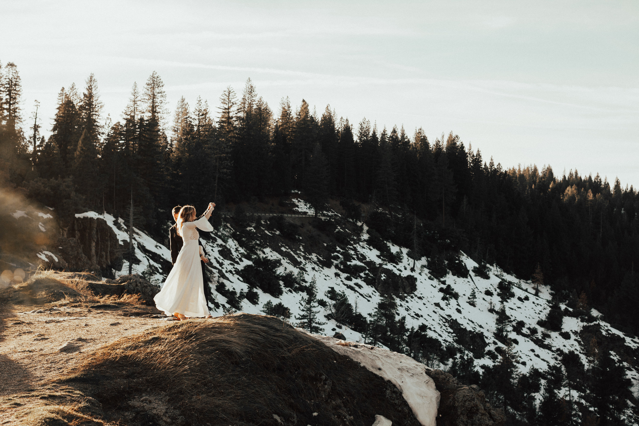 Adventurous couple dancing on the cliffs in nevada city during their elopement.