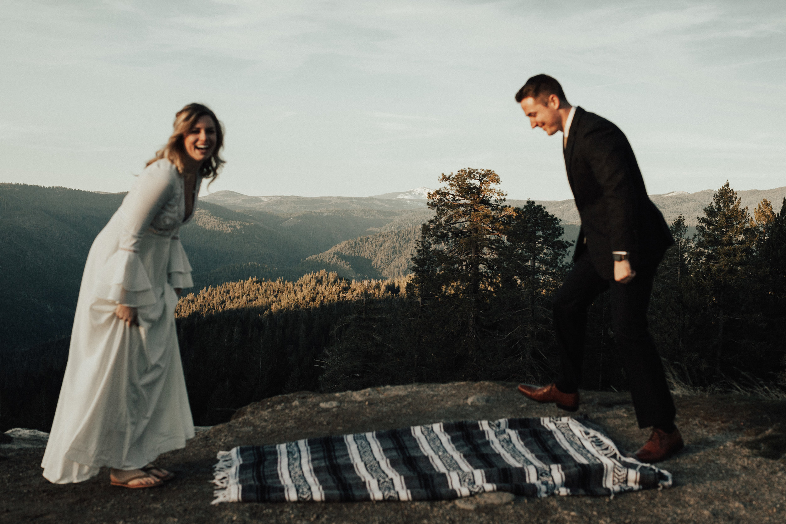 Bride laughing as her groom sets up a blanket to share picnic food and wedding cake ontop of.