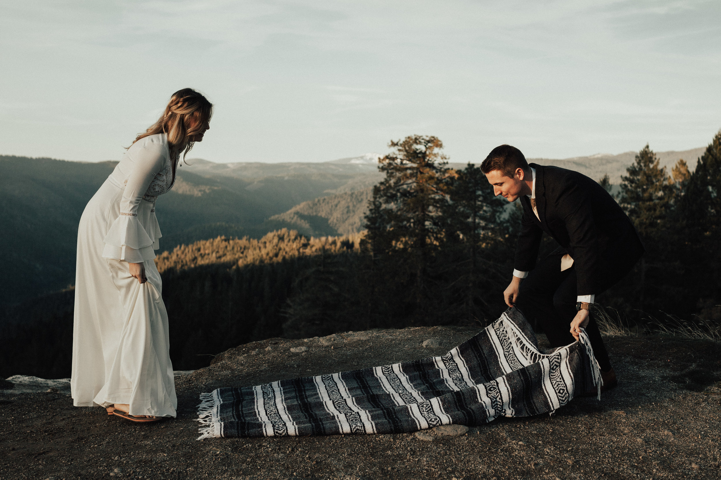 Bride and groom set up a blanket on a cliffside in nevada city near sacramento.