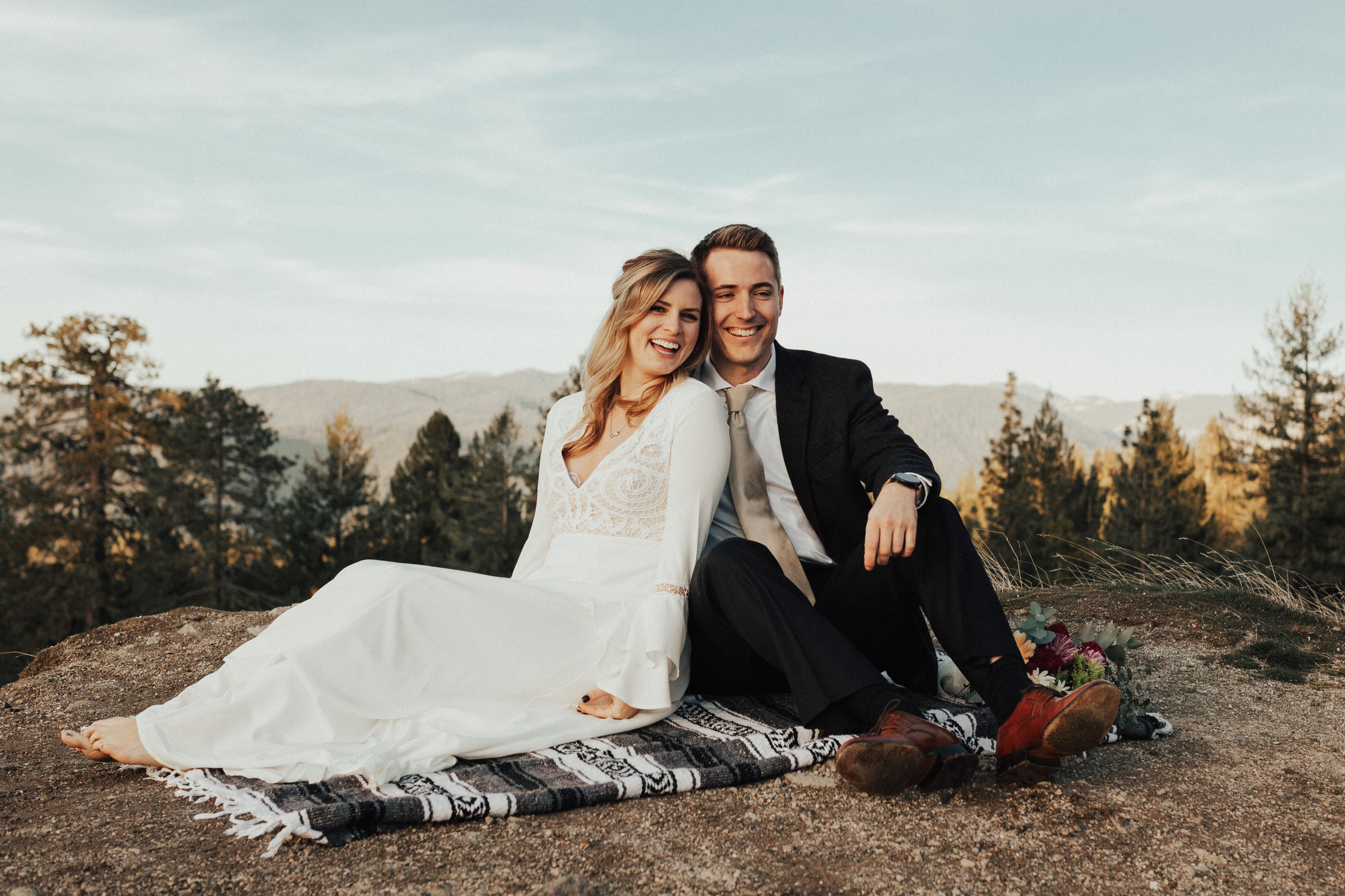 Bride and groom sitting snuggled up on a blanket after just getting married on the cliff side in nevada city, california.