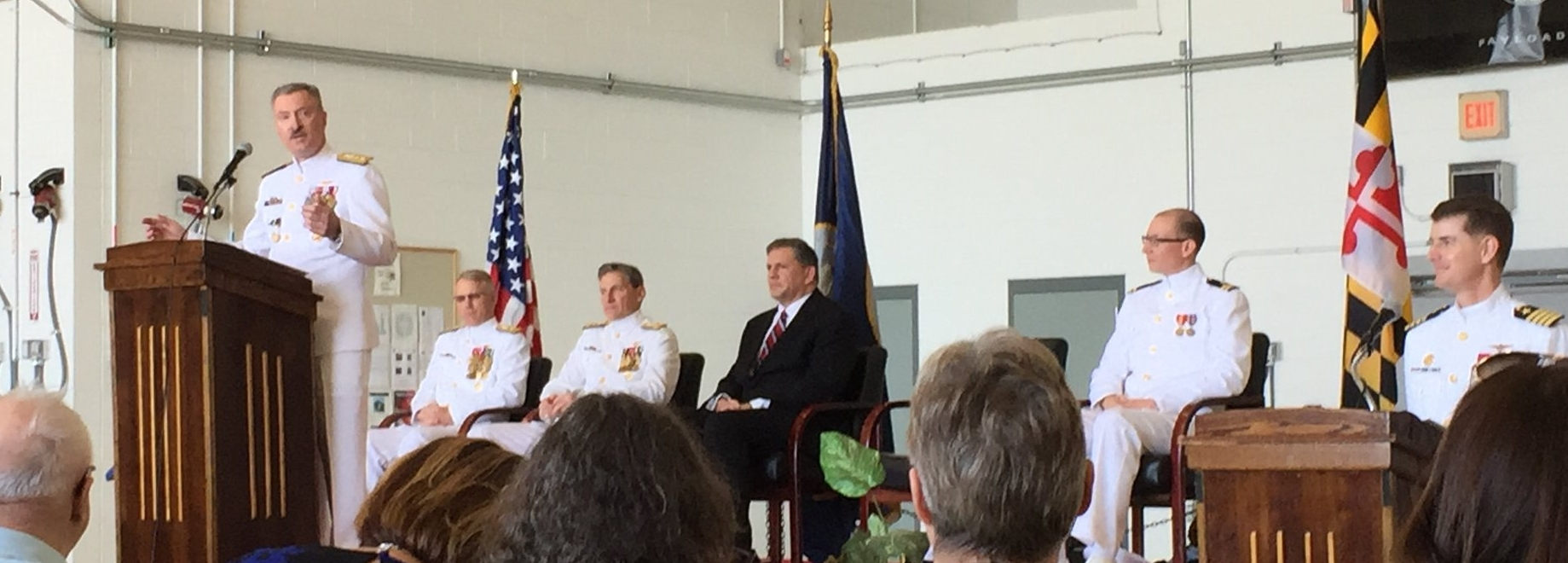 """RADM Mark Darrah, USN, outgoing PEO U&W addresses the crowd with RDML Brian Corey, the new PEO U&W, VADM Paul Grosklags head of NAVAIR, and ASN RDA Jim """"Hondo"""" Guerts among others in attendance (May 3, 2018)."""