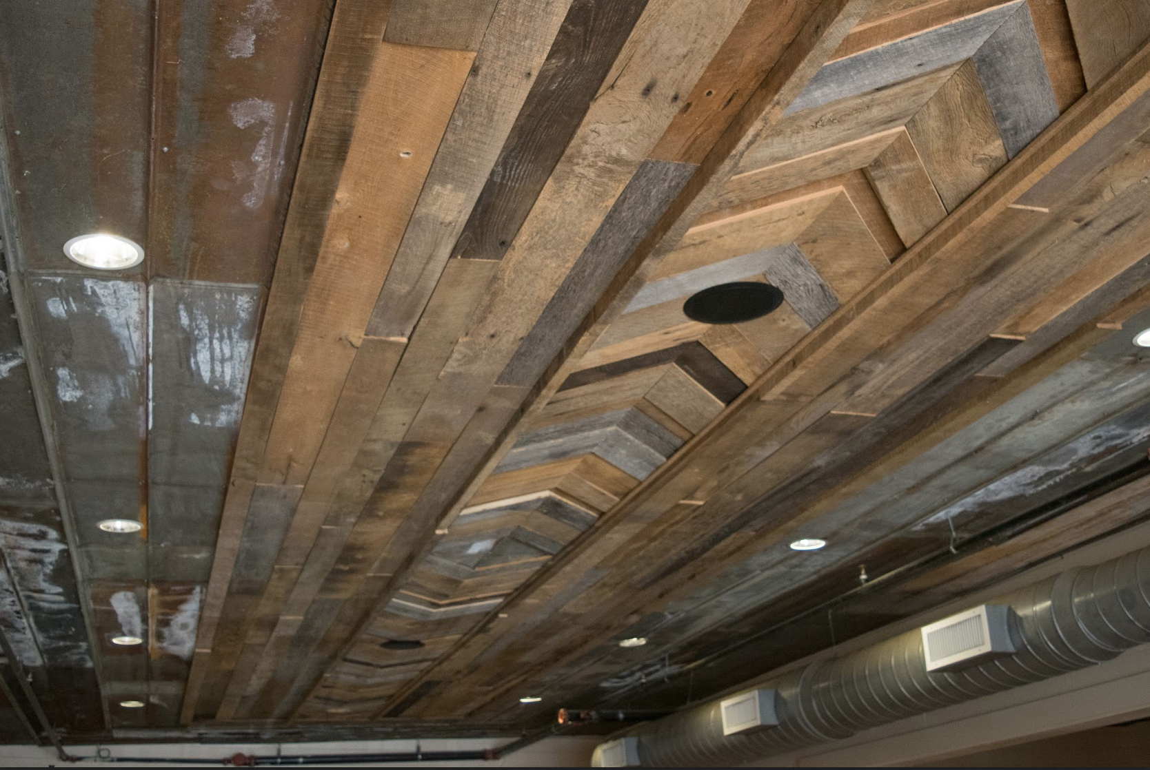 The ceiling of the private dining rooms are covered with a design of reclaimed barn wood and tin