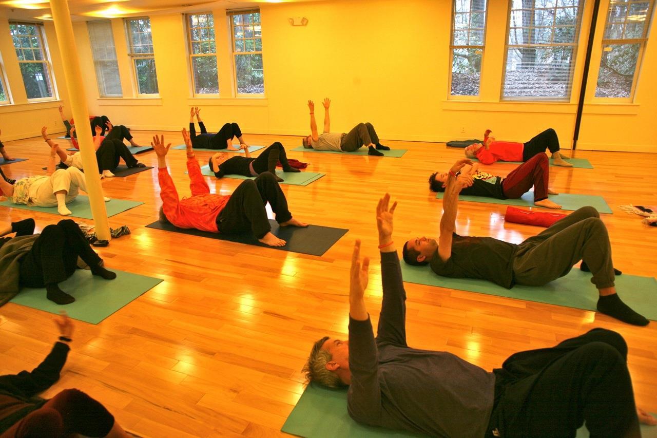 Yoga students on backs with arms overhead