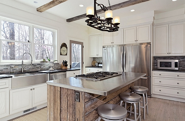 A stainless steel countertop on top of a wooden kitchen island blends the industrial feel of stainless steel with the rustic feel of wood to create a unique design.