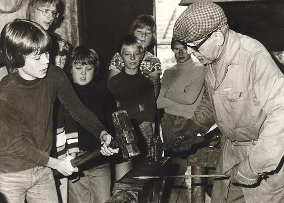 Smedemester Gunnar Hansen med elever fra Blovstrød Skole i smedjen på hjørnet af Kongevejen og Blovstrød Byvej. 1977. Foto: Lokalhistorisk Arkiv.