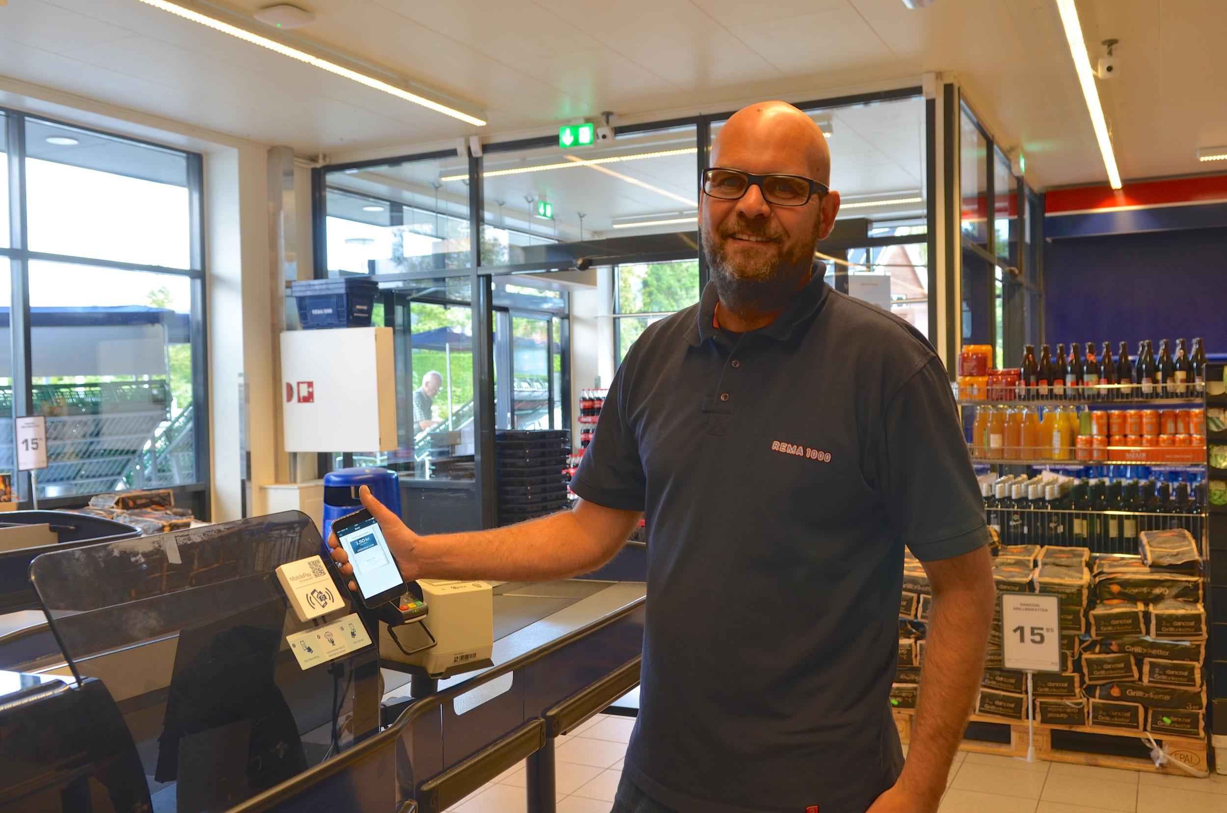 Købmand Lars Bo Christensen - fra Rema 1000 i Blovstrød - viser her, hvor enkelt det er at betale med 'Mobile Pay': Du holder blot din smartphone op foran scanneren og godkender beløbet. Foto: AOB