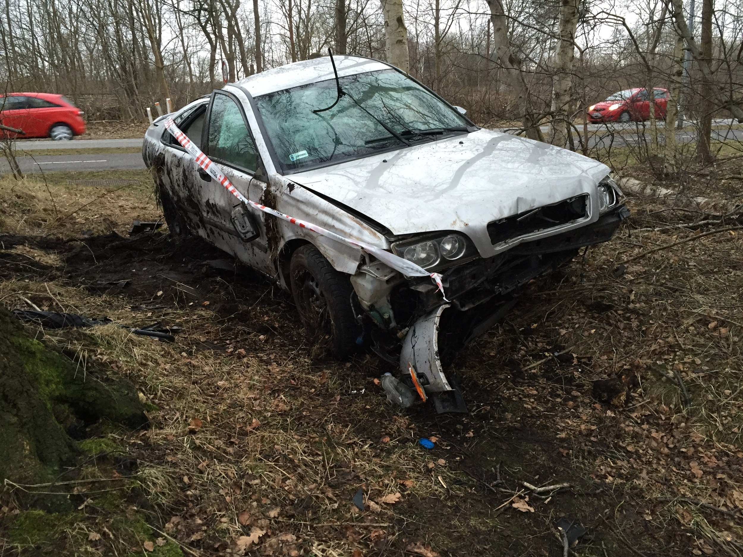 Den havarerede bil så forfærdelig medtaget ud med bildele spredt ud over arealet. Politiet havde været på stedet og afmonteret nummerpladerne. Foto. AOB