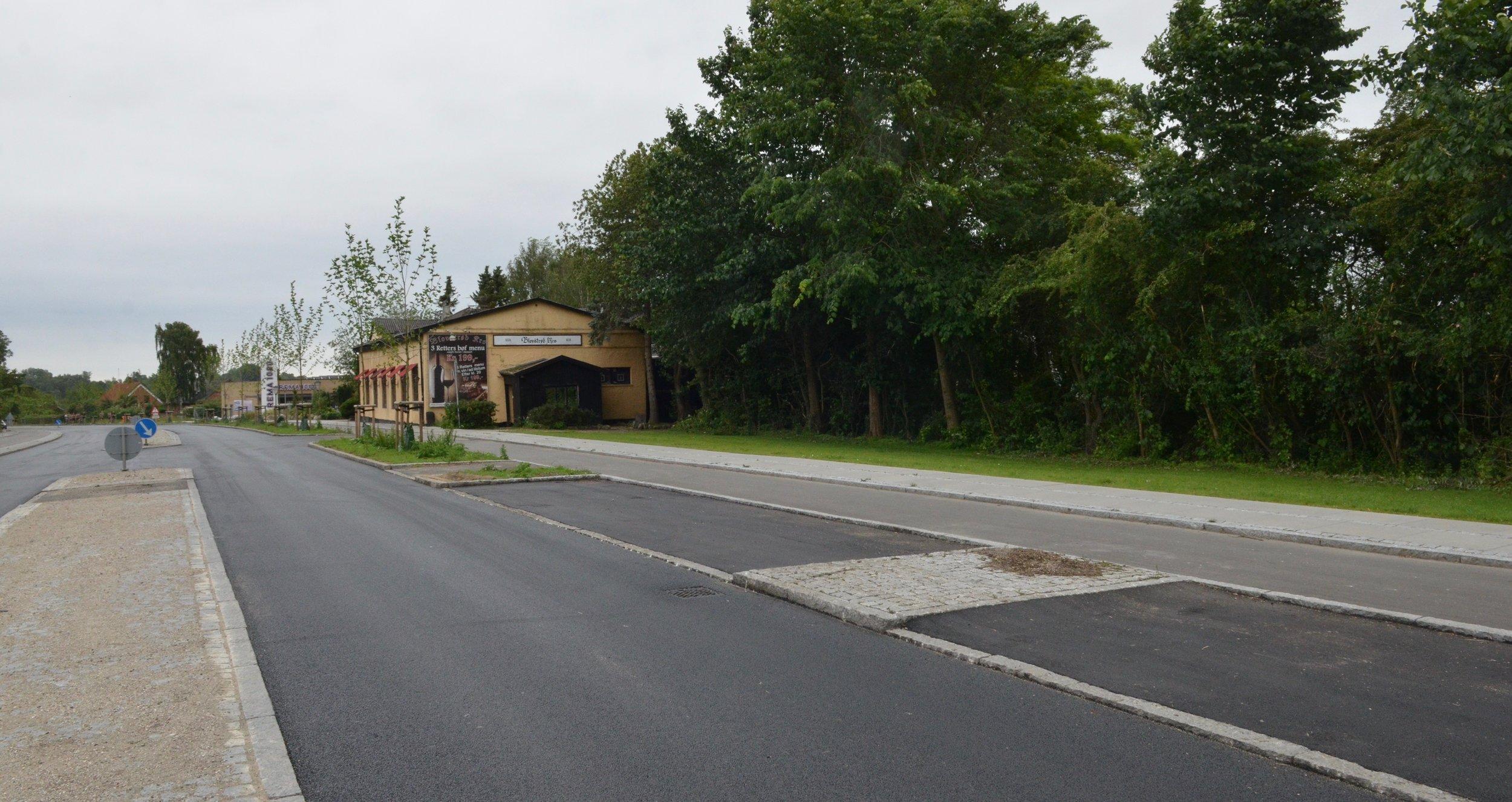 Overfor bageren blev granit-markeringen ikke sænket/fjernet mellem de to parkeringslommer, men der er dog udført en lille asfaltrampe op mod den hævede flade  . Som det ses, er kørebanens asfalt helt sort, men vil lysne med tiden, når topfilmen er slidt af.Foto: AOB