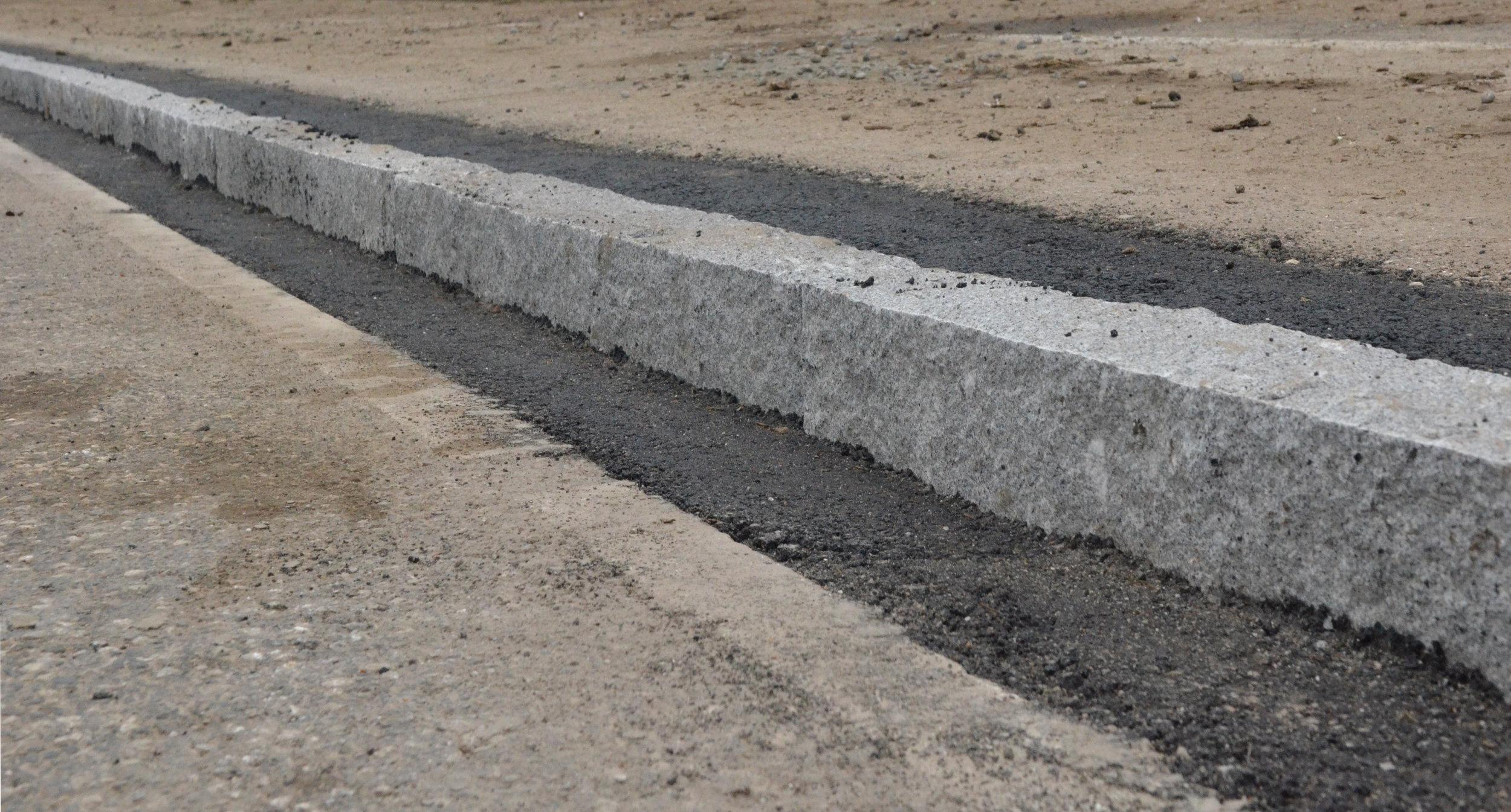 På den vestlige side af Kongevejen er der opsat en ny granitkantsten - men mod øst har man - ind til videre - bibeholdt den gamle delvis forvitrede betonkantsten.Foto: AOB