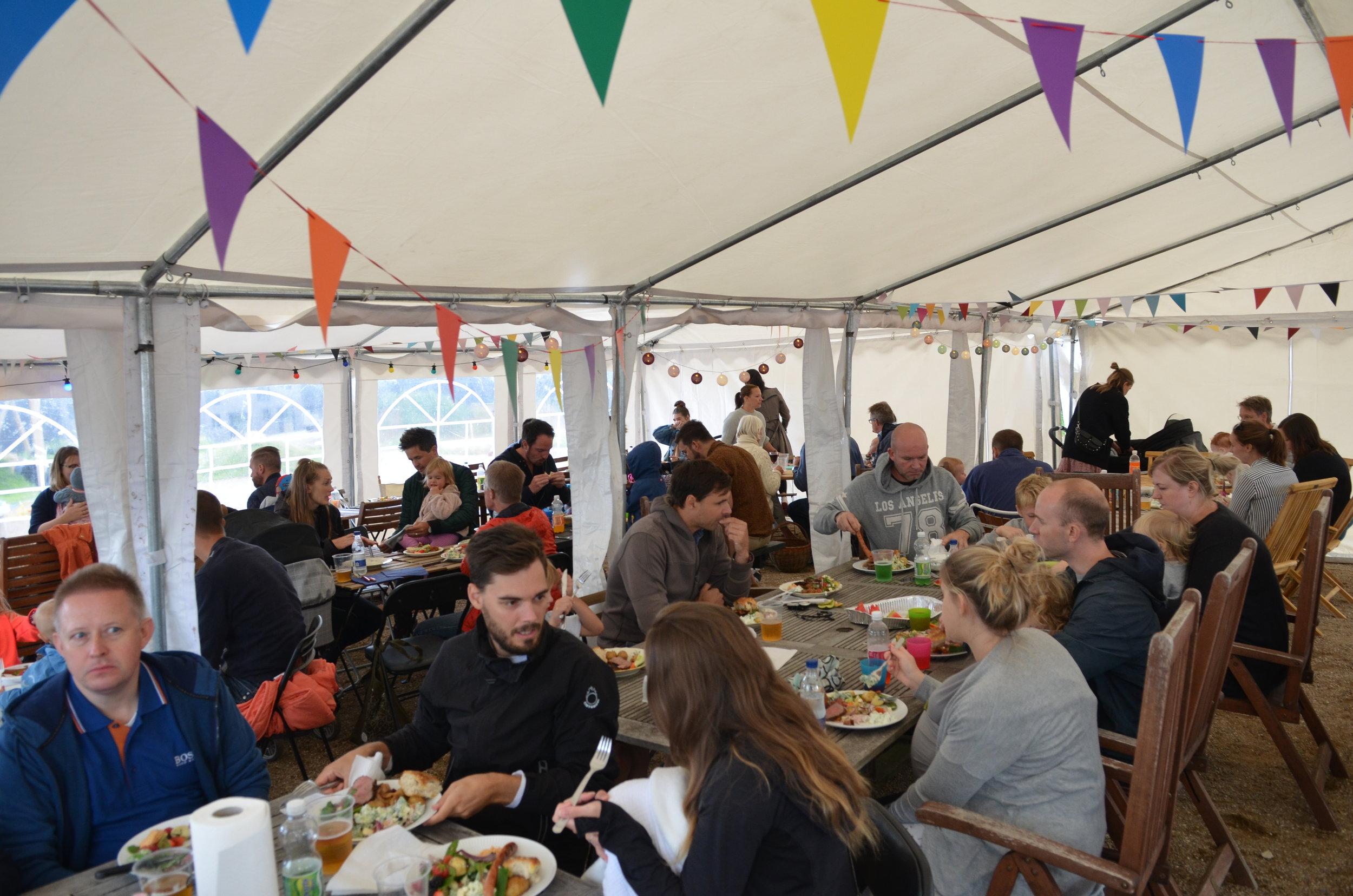 Alle nåede at komme ind i teltet for at nyde den dejlige mad, inden det rigtig begyndte at regne. Foto: AOB
