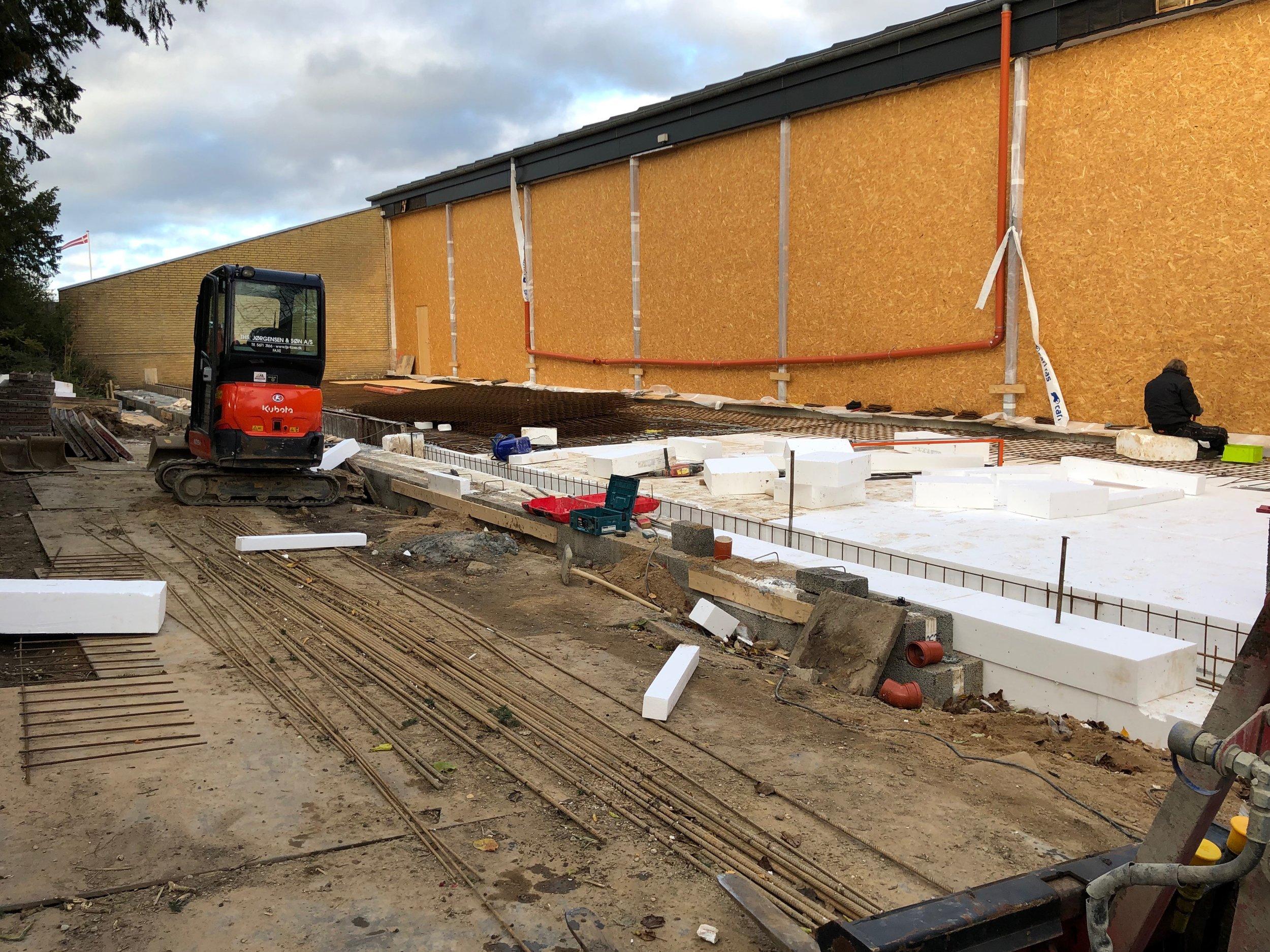 Svømmehallens store vinduer mod syd er nu lukket med midlertidige spånplader. Når beton-kanonen ankommer på fredag, vil en slange på næsten 50 meter føre den flydende beton helt ind på det nye, isolerede og armerede gulv. Foto: AOB