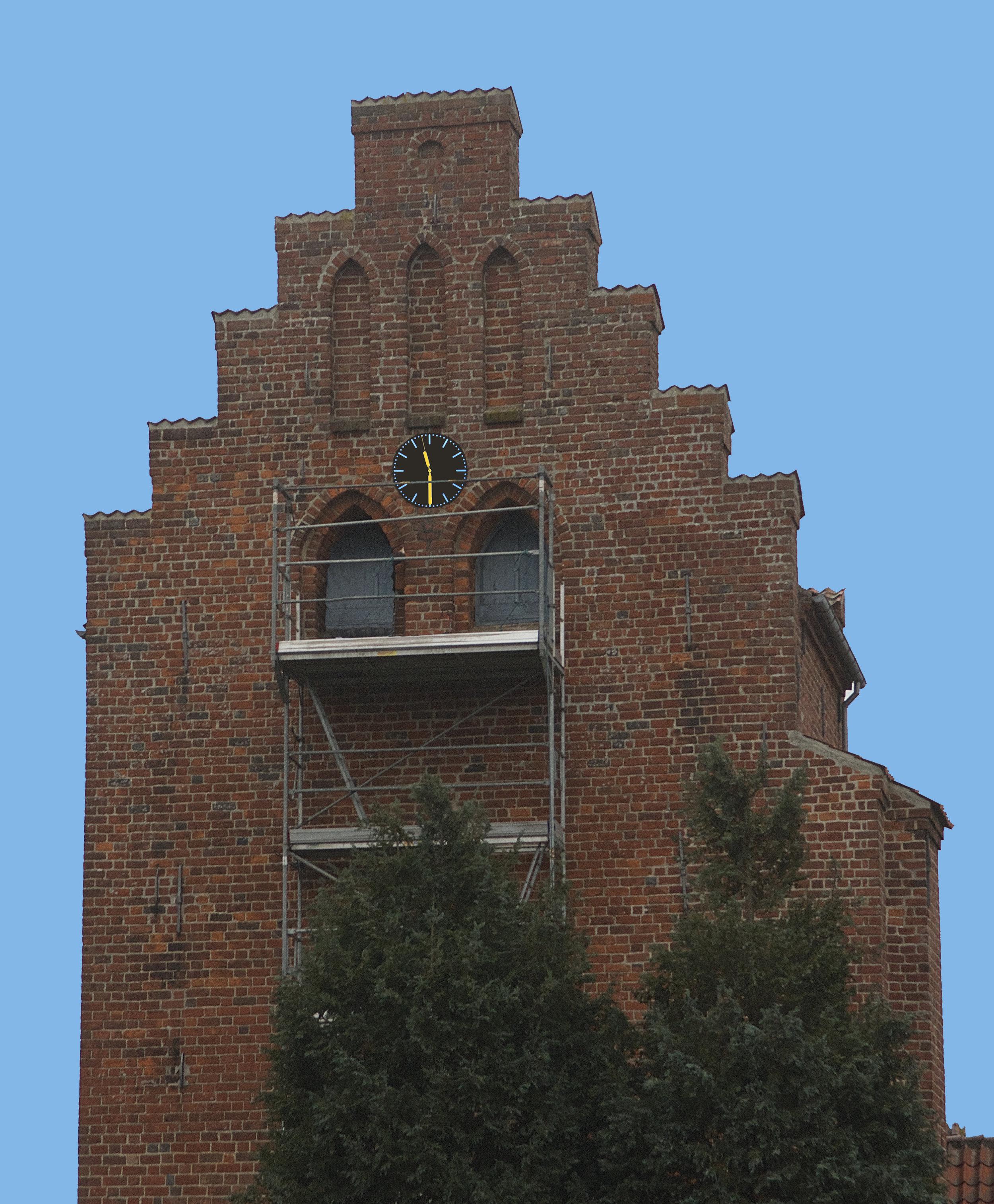 Flere borgere har spurgt, hvorfor der var stillet stillads op ved kirketårnets gavl - men udskiftningen af uret giver nu forklaringen. Foto: AOB