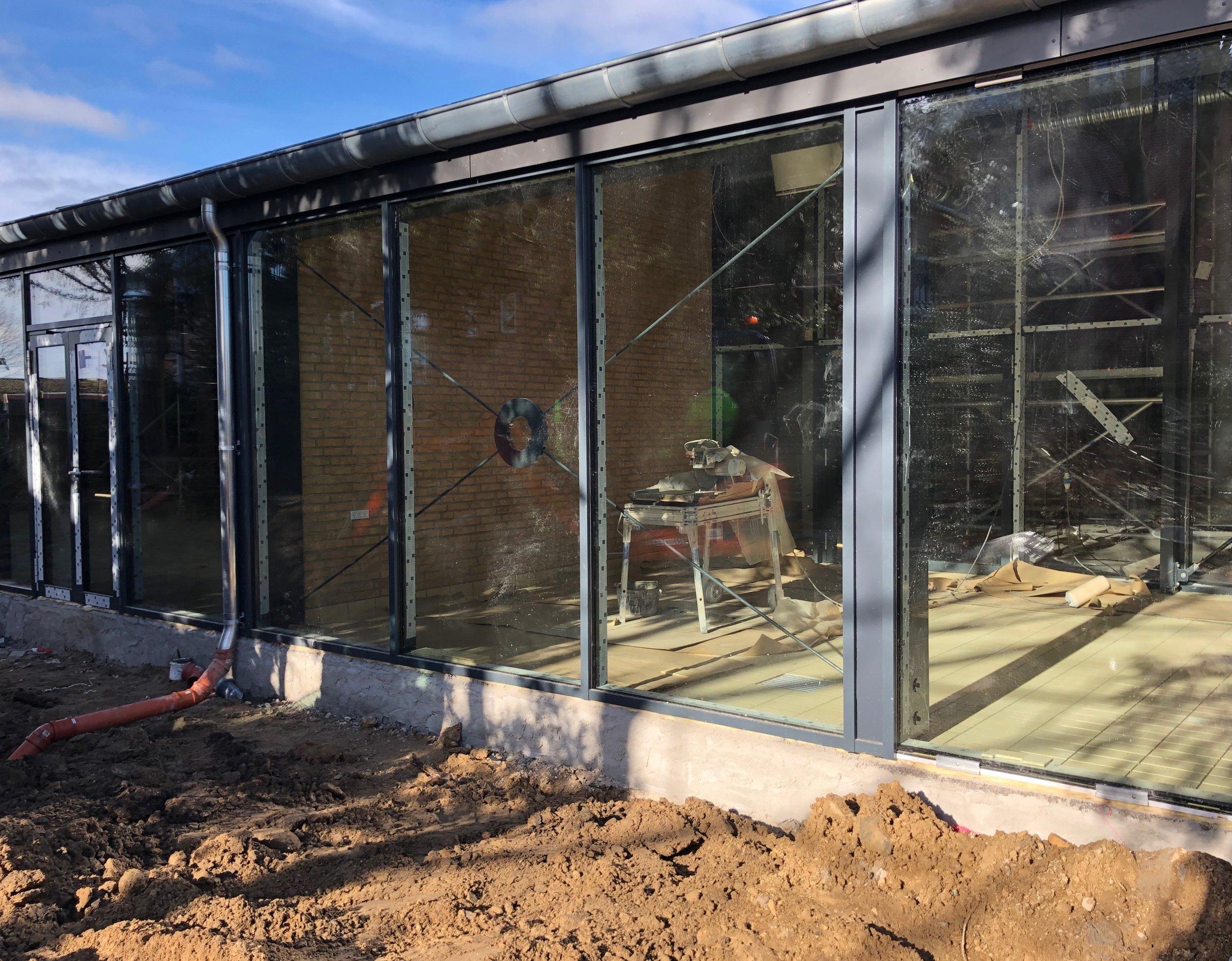 Stilladset er fjernet, så man idag rigtig kan se den nye lange glasfacade. Foto: AOB