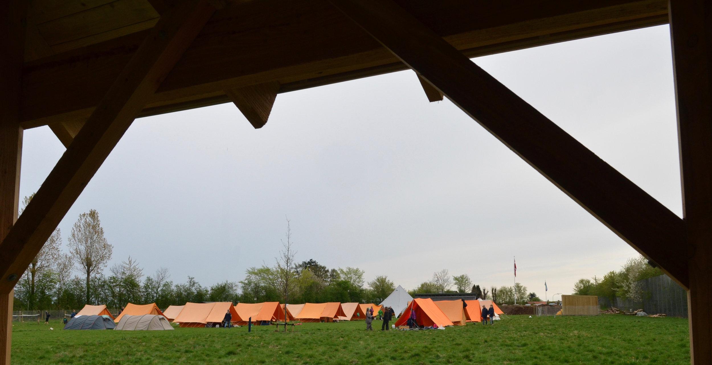 Selvom det var styrtende regn lørdag formiddag, holdt det ikke de friske spejdere tilbage, som hurtigt fik rejst en kæmpe orange teltby. Foto: AOB