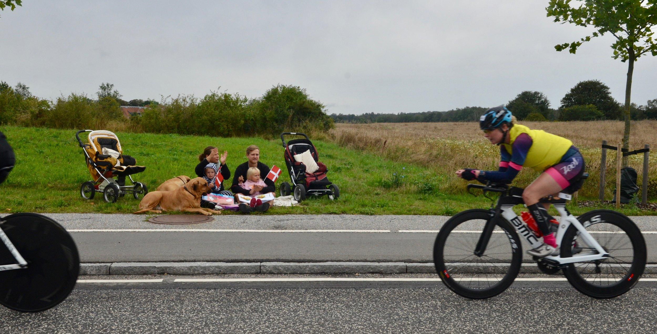 Mange Blovstrød-borgere havde i dagens anledning taget opstilling langs Kongevejen med børn og hunde for at følge Ironman-cykelløbet. Foto: AOB
