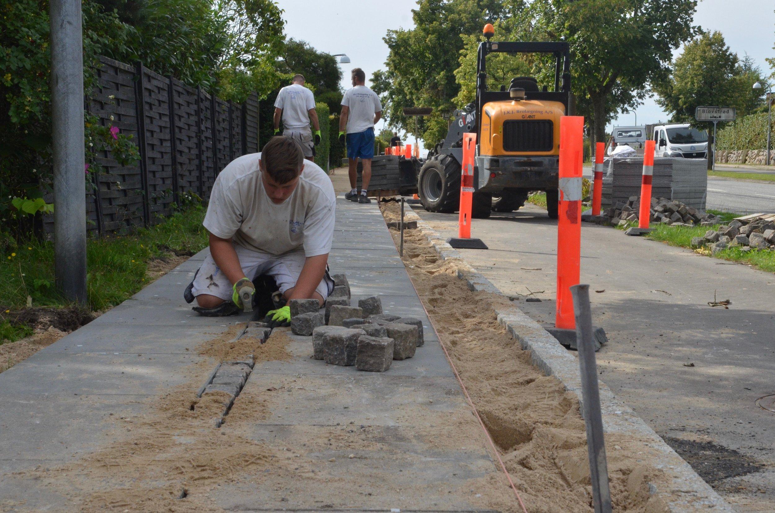 Nu bliver der sat nye granitkantsten op mellem cykelstien og det nye fortov, som udføres med nye betonfliser og med genanvendelse af de gamle chaussésten - det bliver rigtig fint. Foto: AOB