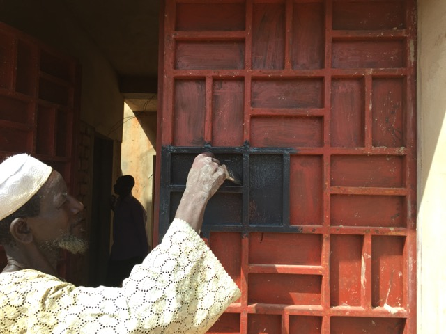 New fabricated entrance door being painted at the Niamey2000 project. Image by Mariam Kamara ©atelier masomi