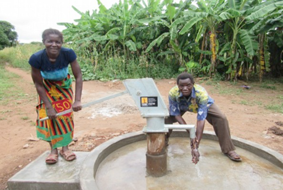 With smiling faces, the residents come to pump water from the well.