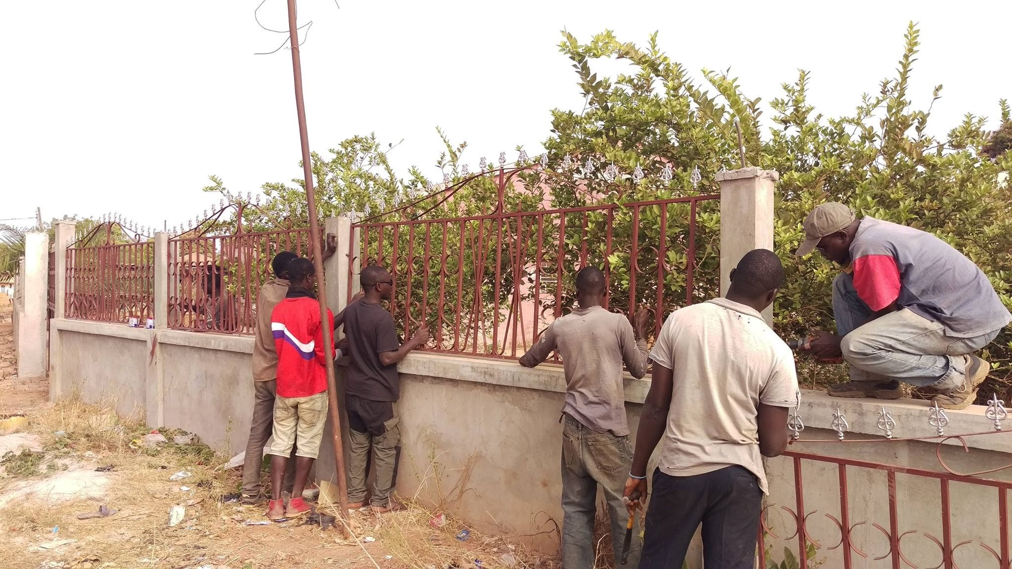 Welding students installing a fence at a home in Canchungo.