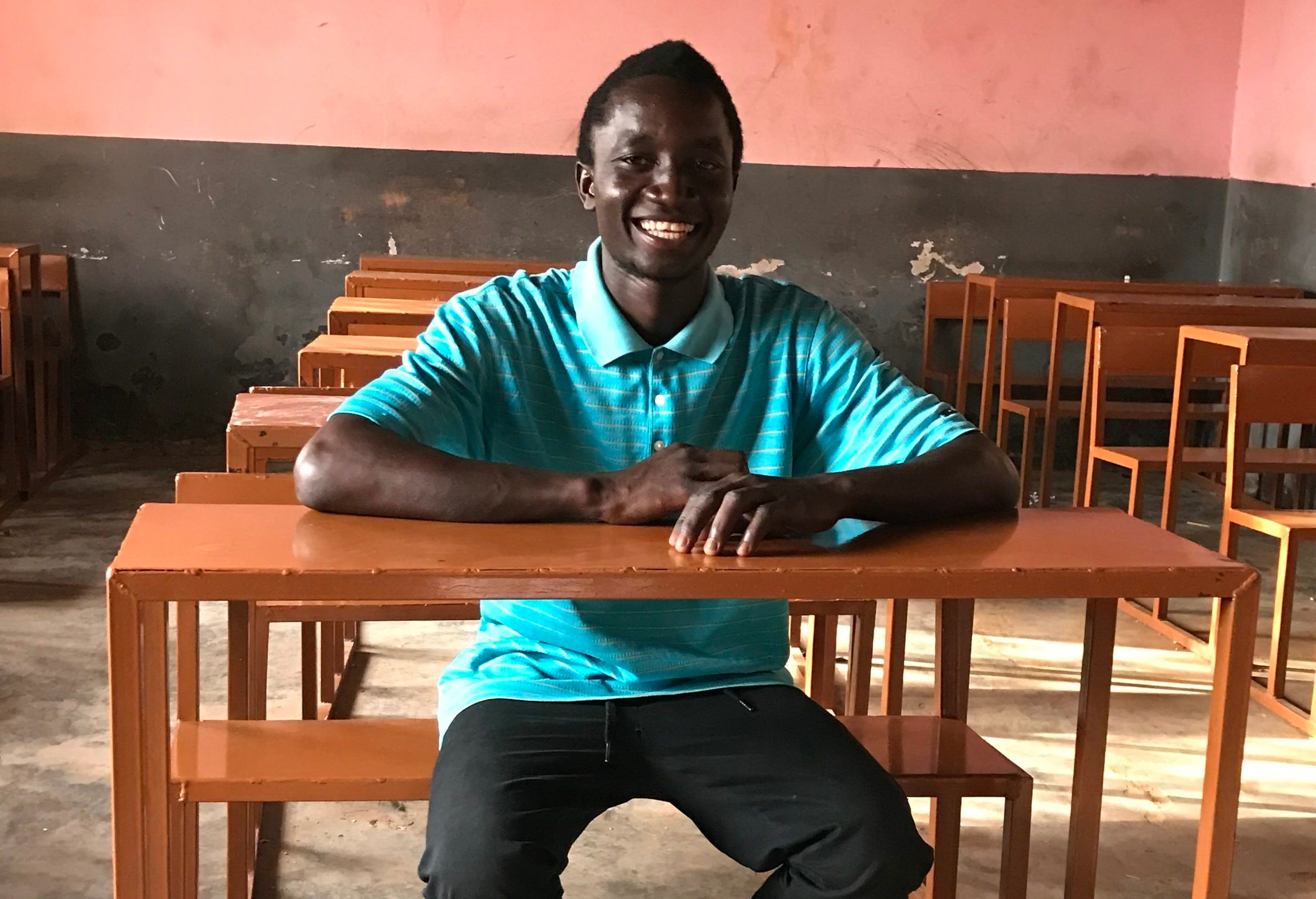 WAVS Welding graduate Erickson Sanhá smiles as he shows off some of the 70 school desks that he and his fellow graduates were hired to build for a local school.