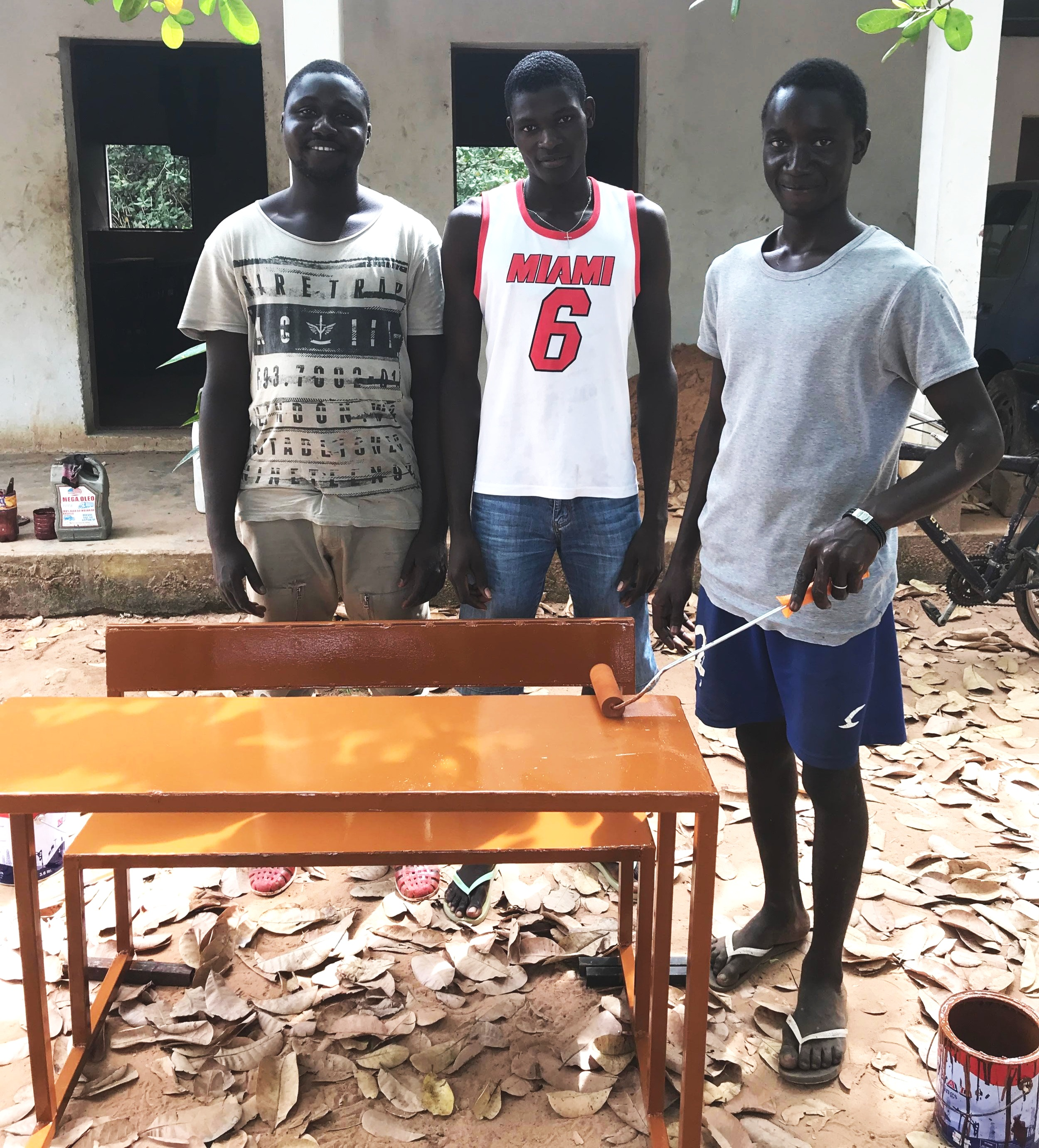 Erickson and his fellow graduates finish painting one of the 70 desks a local school hired them to build.