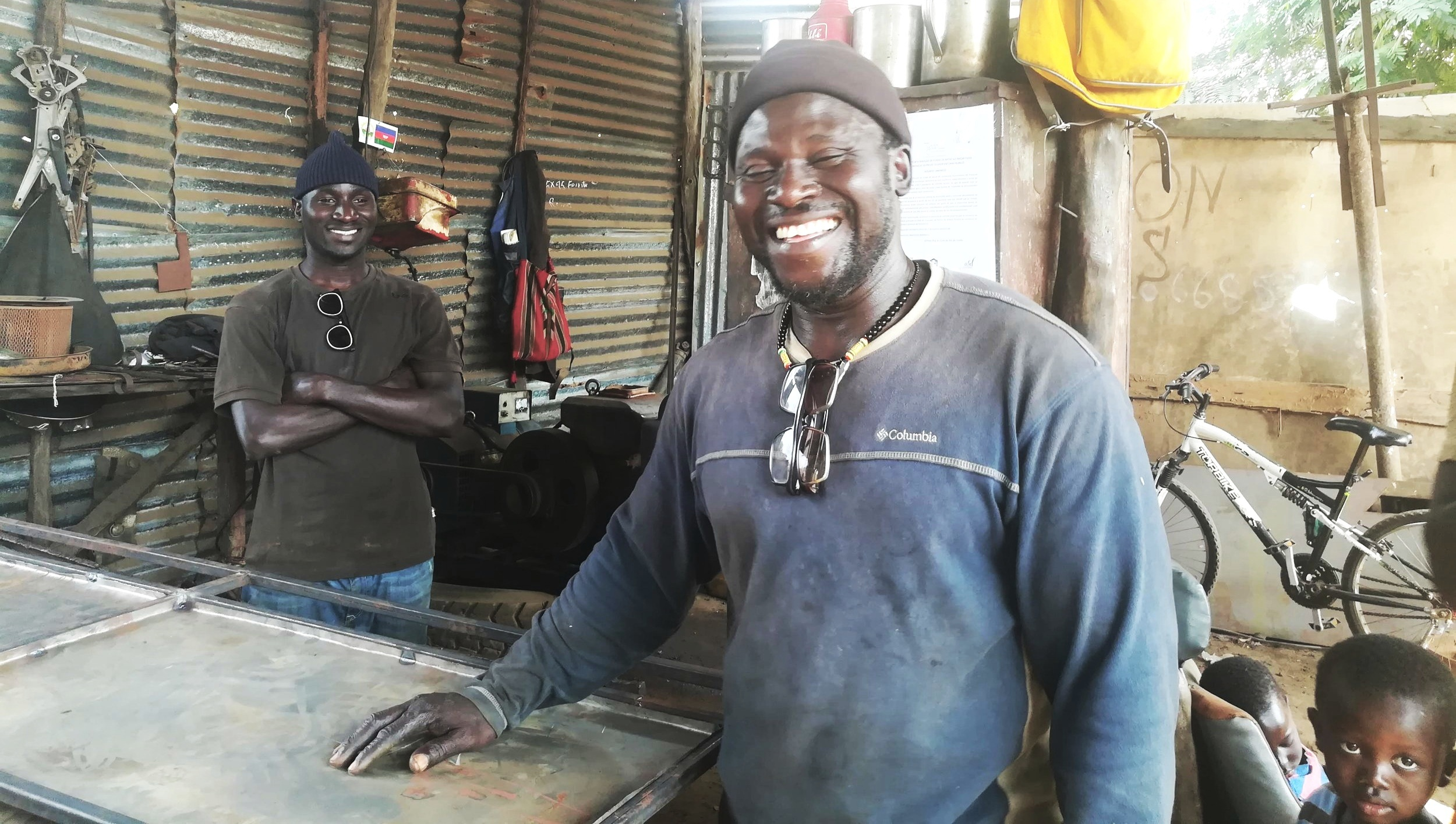 Ciro (right) and his former apprentice, Nilton (left), smile as they show off their welding workshop in West Africa. Ciro attended the WAVS Vocational School so he could grow his business and provide for four orphaned children.