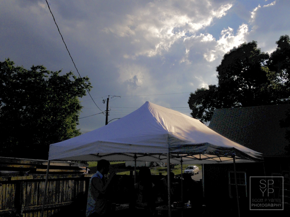 The setting sun's last rays shine on the pop-up tent in the backyard.