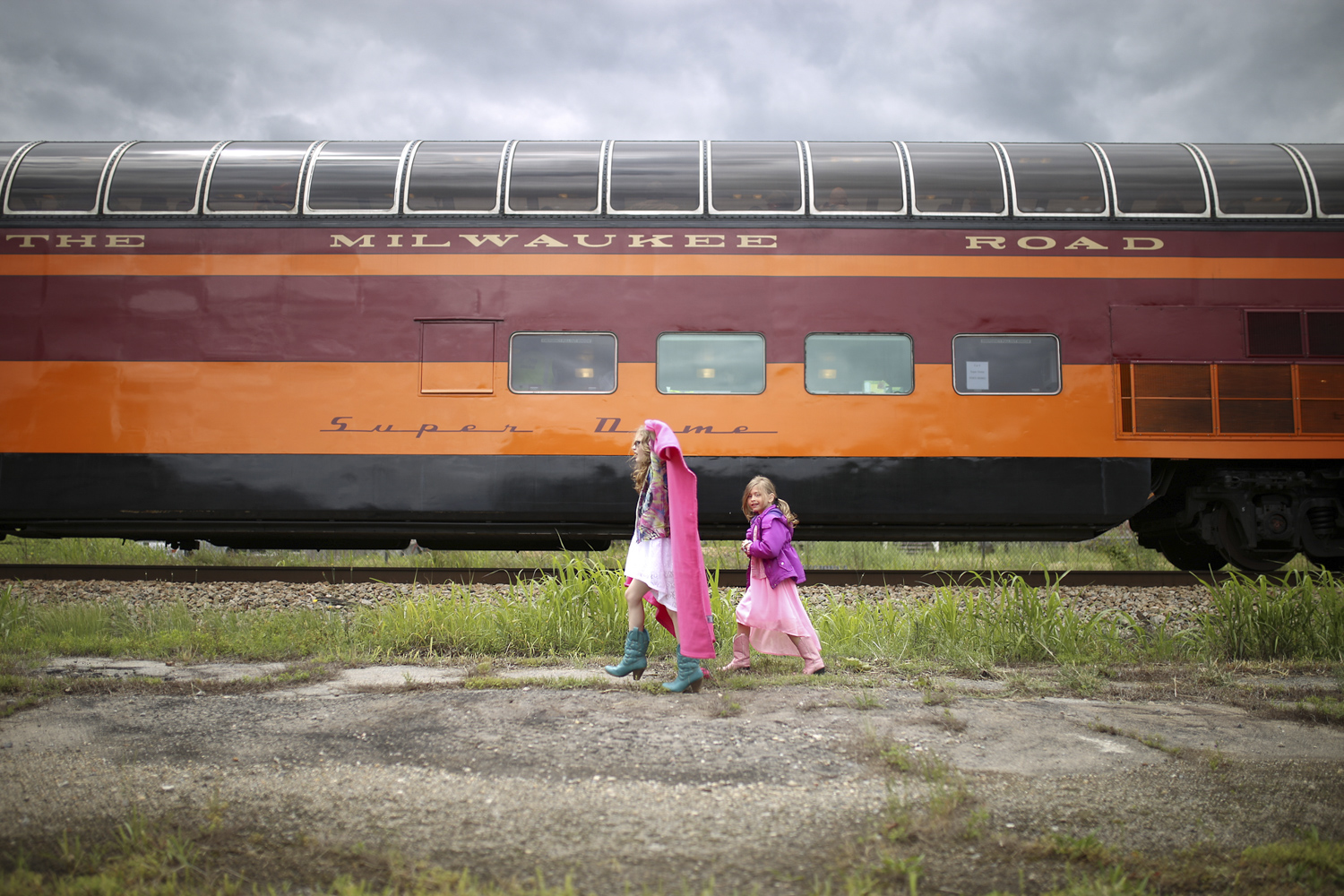 Sisters Hailey Hoffman, 9, left, and Melanie, 7, from Colonial Heights, run to catch up to the front of the Class J steam locomotive Norfolk and Western 611 as it slows to a stop at Union Station in Petersburg on Saturday, May 6, 2017. [Scott P. Yates/progress-index.com]