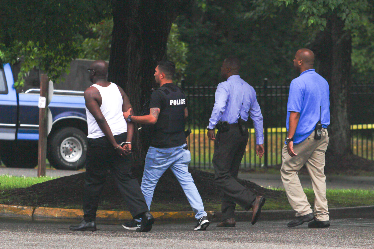 Petersburg police lead away a man arrested after a brief car and foot pursuit in the Ivy Gates Apartments near S. Sycamore Street in Petersburg on Monday, June 5, 2017. The man is suspected of robbing the SunTrust Bank on W. Washington Street earlier in the day. [Scott P. Yates/progress-index.com]