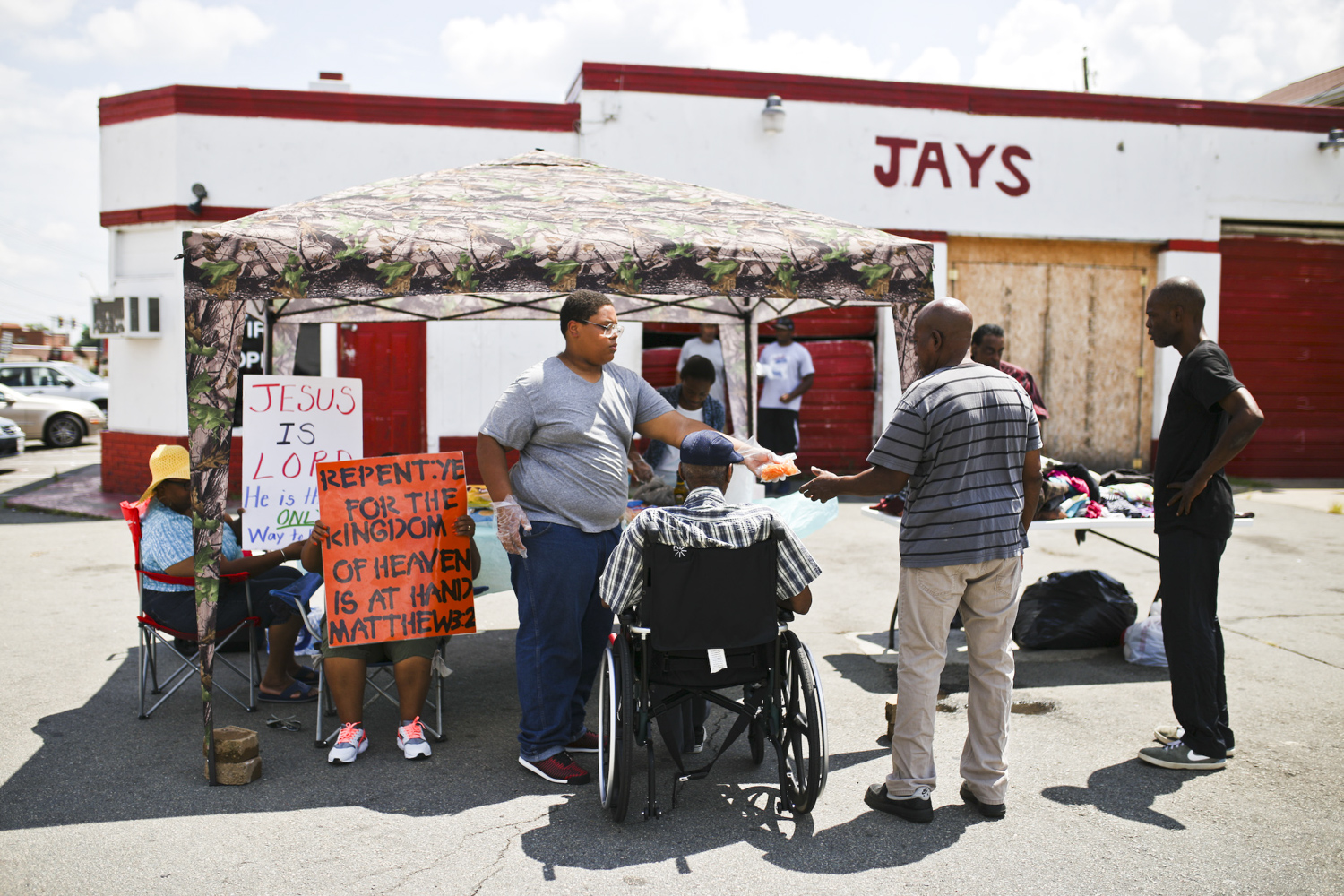 Phillip Bailey Jr., center, hands out a hot dog to people who walked by the House of Wisdom church's food and clothing giveaway stand on the corner of Wythe and Sycamore Streets on Saturday morning. [Scott P. Yates/progress-index.com]