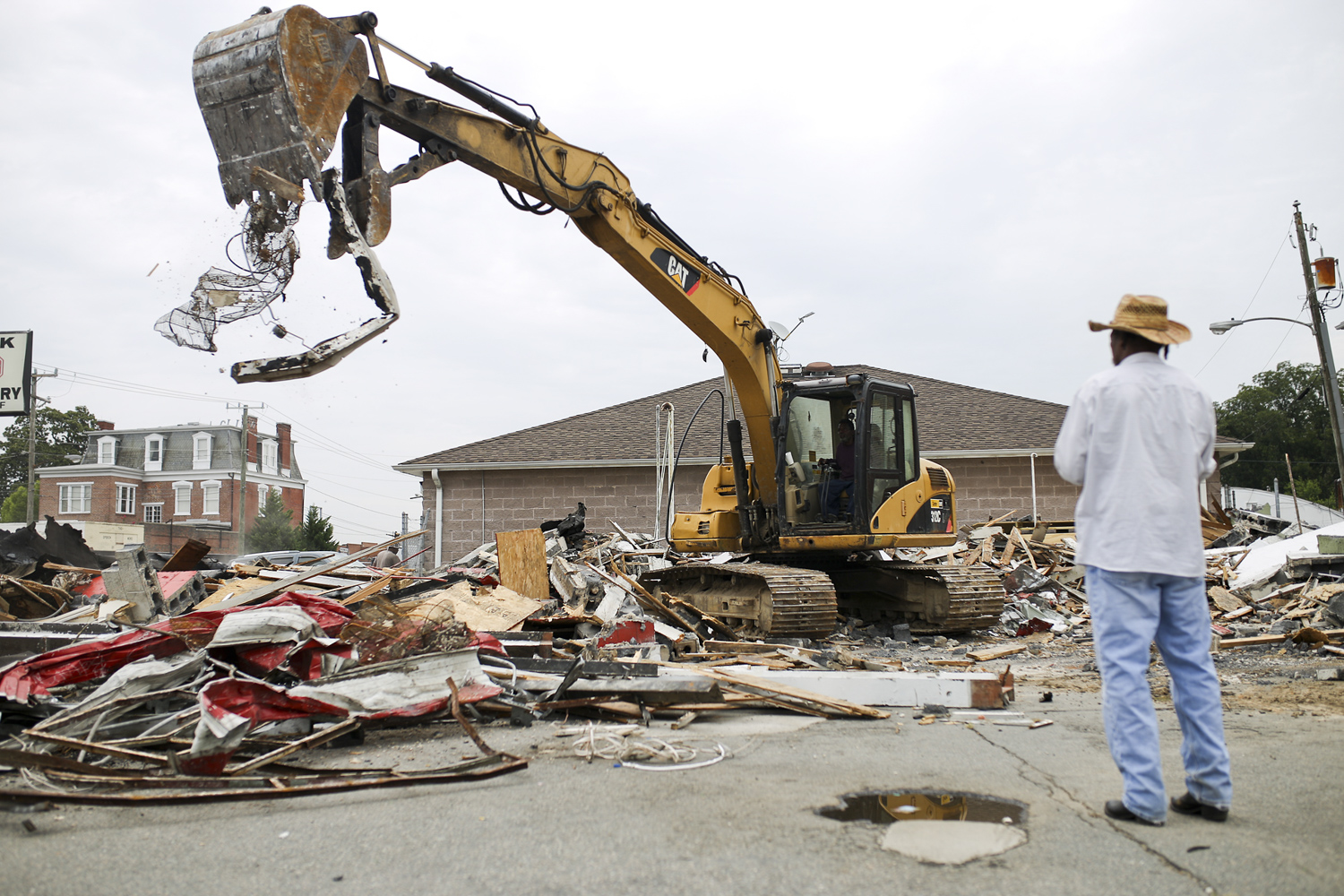 Joe Chamberlain, right, from Petersburg, a worker with Jones Trucking and Hauling, watches machine operator Ernest Jones demolish the Jays tire shop that once stood for years on the corner of Wythe and N. Sycamore Streets in Petersburg on Monday, August 14, 2017. [Scott P. Yates/progress-index.com]