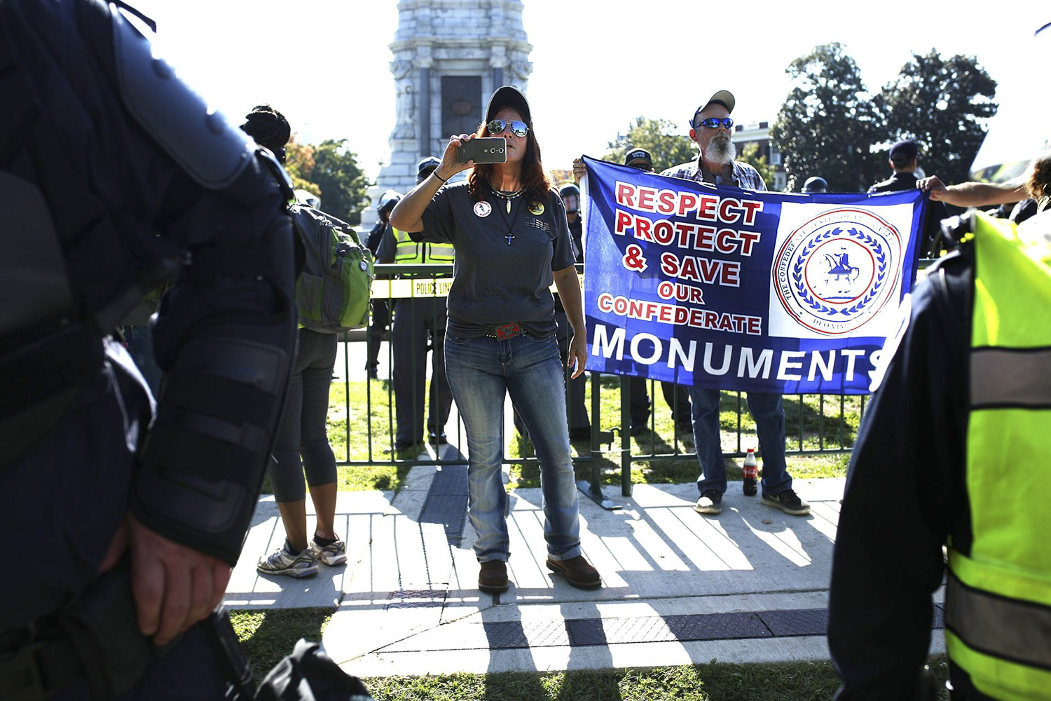 Tara Brandau, center, and other members of CSA II: The New Confederate States of America, rally while surrounded by local and state law enforcement in the shadow of the Robert E. Lee statue on Monument Avenue in Richmond on Saturday, Sept. 16, 2017. [Scott P. Yates/progress-index.com]