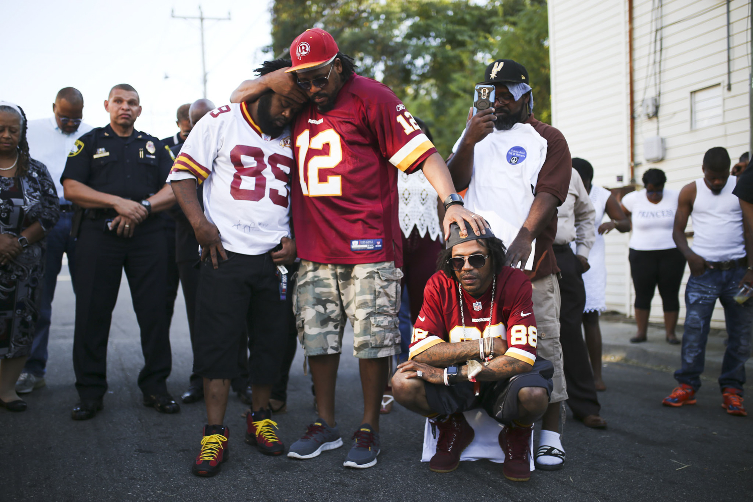 The three surviving brothers of Delqukis Ruffin, who was slain a week earlier, from left, Delveccio, Dondelprecio, and Damion, kneeling, who embrace during a moment of prayer during a vigil for Delqukis Ruffin on Harding Street in Petersburg on Sunday, Sept. 24, 2017. [Scott P. Yates/progress-index.com]