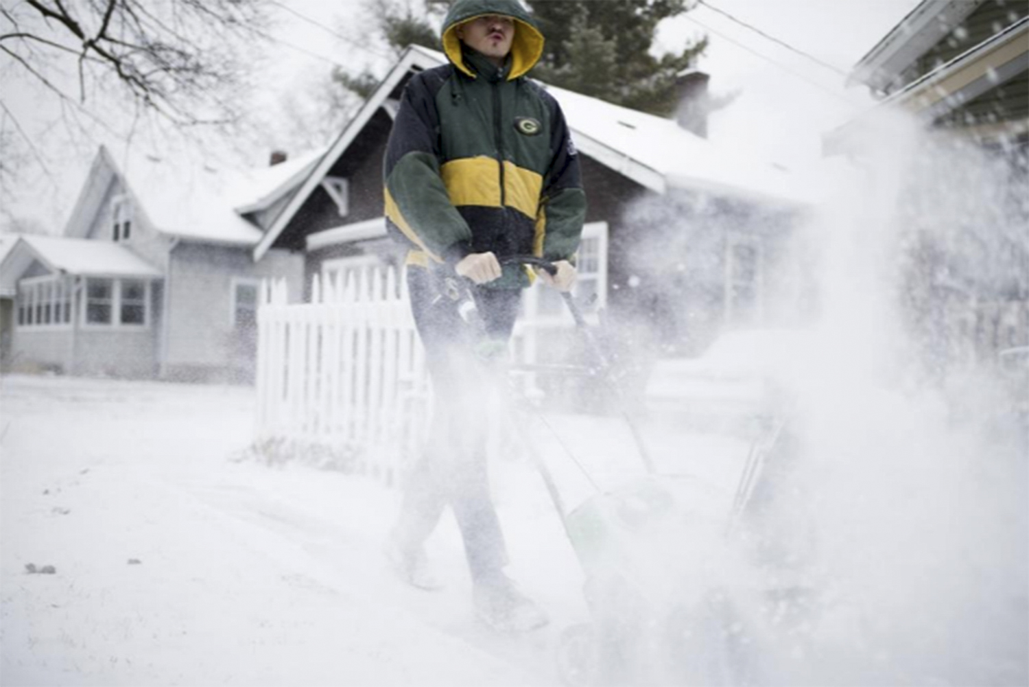Rockford resident Fritz Marlow clears away snow from his neighbors' properties near Woodruff Avenue and Broadway on Sunday, Dec. 24, 2017, in Rockford. [Scott P. Yates/rrstar.com staff]